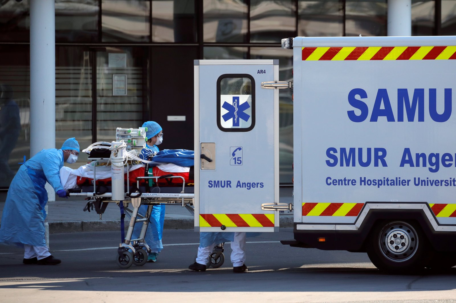 Medical staff move a patient from a special high-speed train to an ambulance during a transfer operation of people infected with COVID-19, from Strasbourg to hospitals in western France, Angers, Thursday, March 26, 2020. (Reuters Photo)