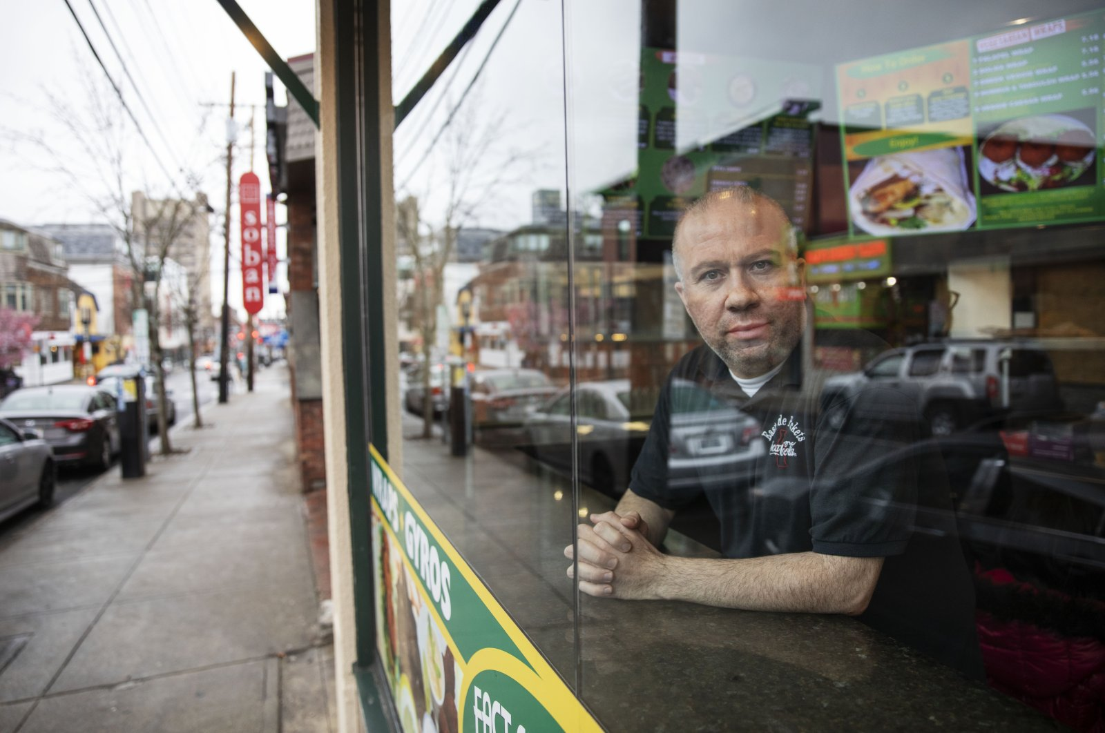Paul Boutros, the owner of East Side Pockets, a small restaurant near Brown University, looks out onto an empty street since students were sent home two weeks ago, Wednesday, March 25, 2020, in Providence, R.I. (AP Photo)