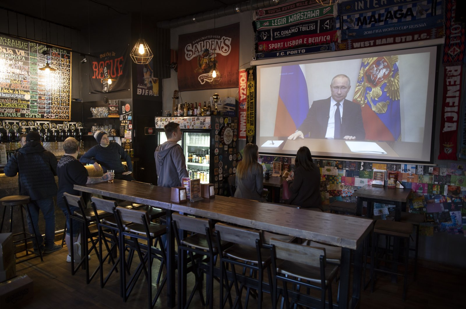 A few visitors and staff of a pub watch the broadcast of Russian President Vladimir Putin addressing Russian citizens on the state television channel in Moscow, Russia, Wednesday, March 25, 2020. (AP Photo)