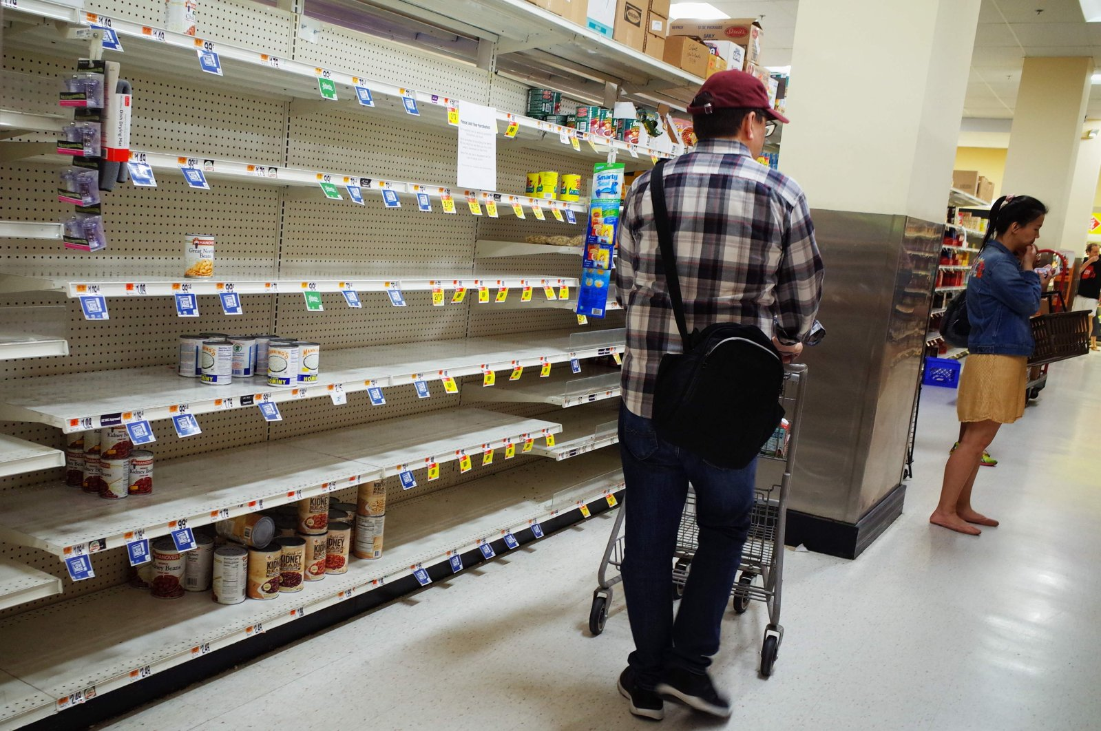 Shoppers are seen wandering next to near empty shelves for canned goods at a supermarket in Washington, DC on March 20, 2020. (AFP FIle Photo)