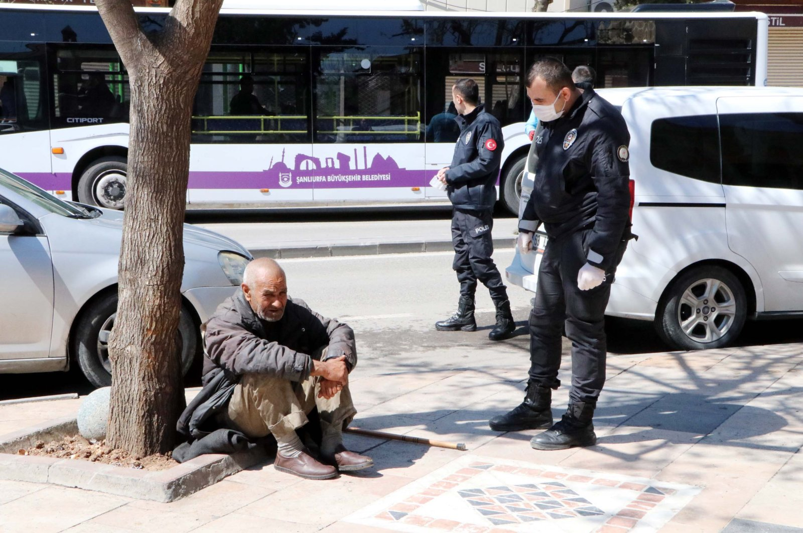 A police officer tries to convince a 68-year-old homeless man to let him take him to a shelter in Şanlıurfa, Sunday, March 22, 2020. (DHA Photo)