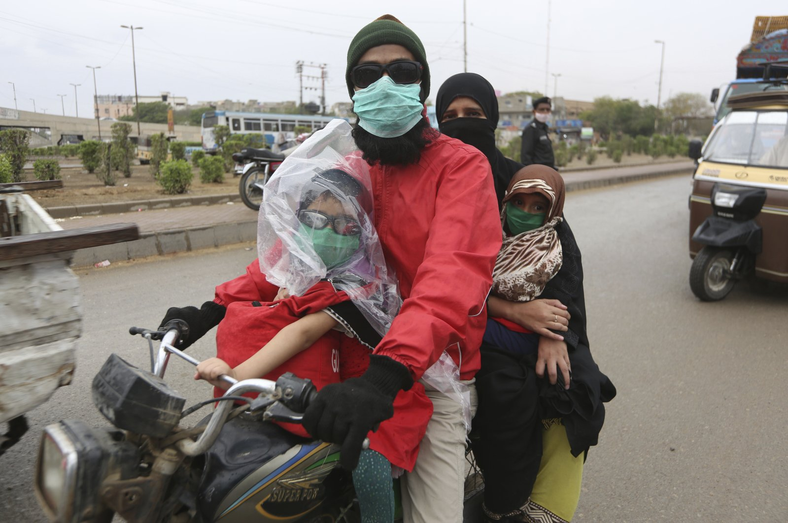 A family travels on a motorcycle wearing face masks during a government-imposed nationwide lockdown, as a preventive measure to contain the coronavirus, in Karachi, Pakistan, Thursday, March 26, 2020. (AP Photo)