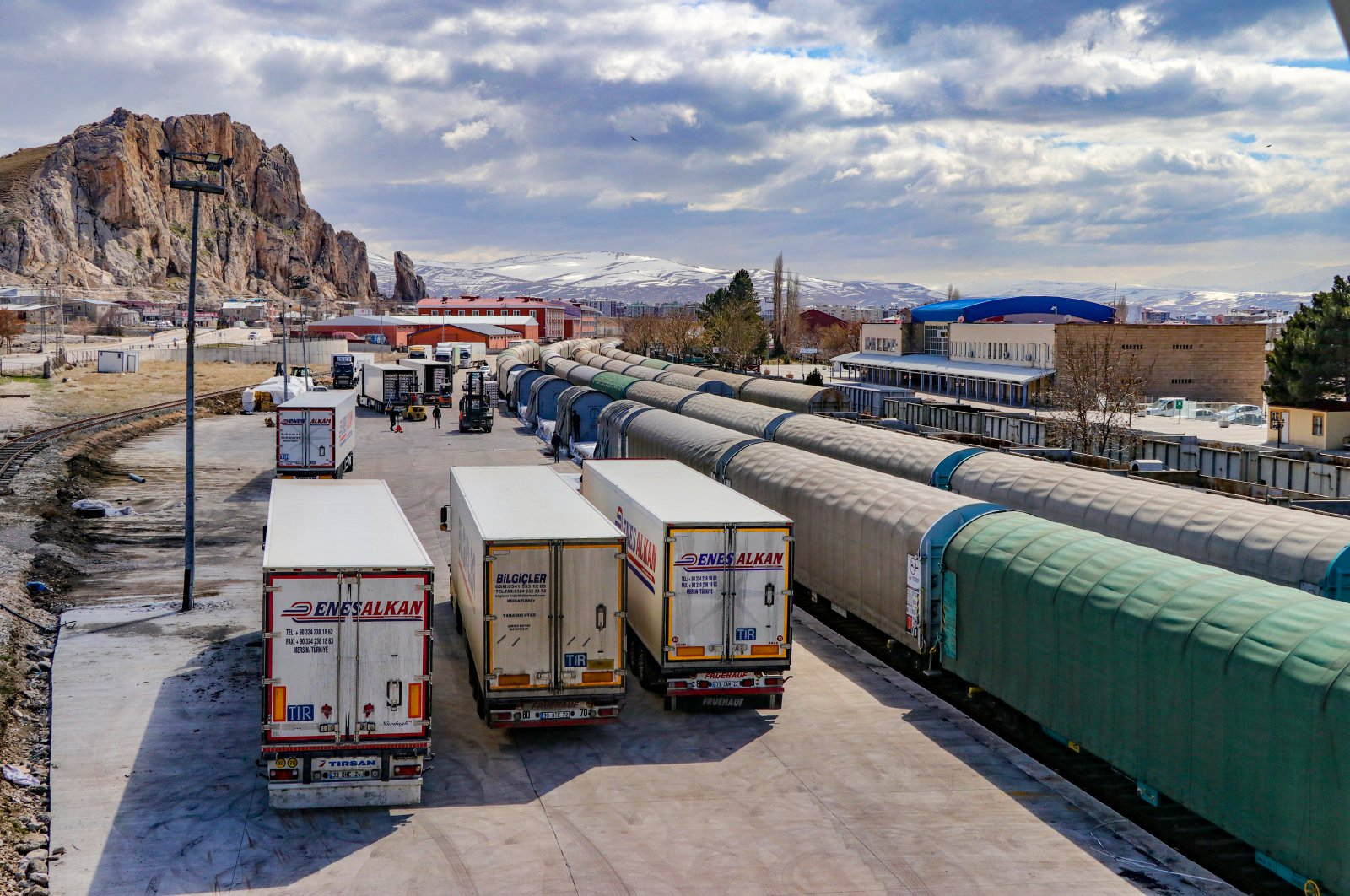 Trucks carrying goods from Turkey's southern province of Mersin and railway cars are seen near a logistics center in the eastern province of Van near the Iranian border, Monday, March 23, 2020. (AA Photo)