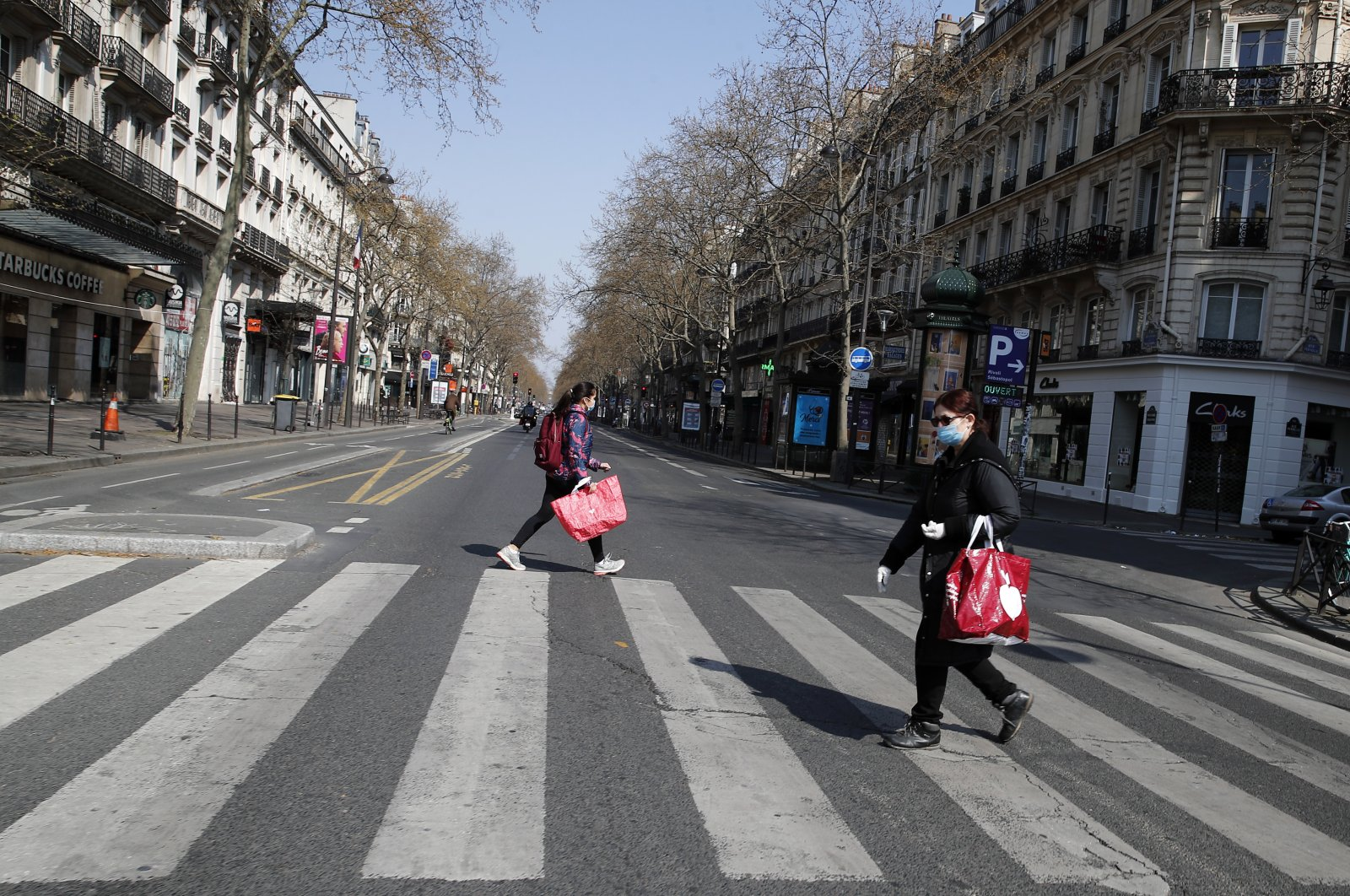 People wearing protective masks cross the deserted Boulevard Sebastopol during the lockdown of coronavirus, Paris, Friday, March 27, 2020. (AP Photo)