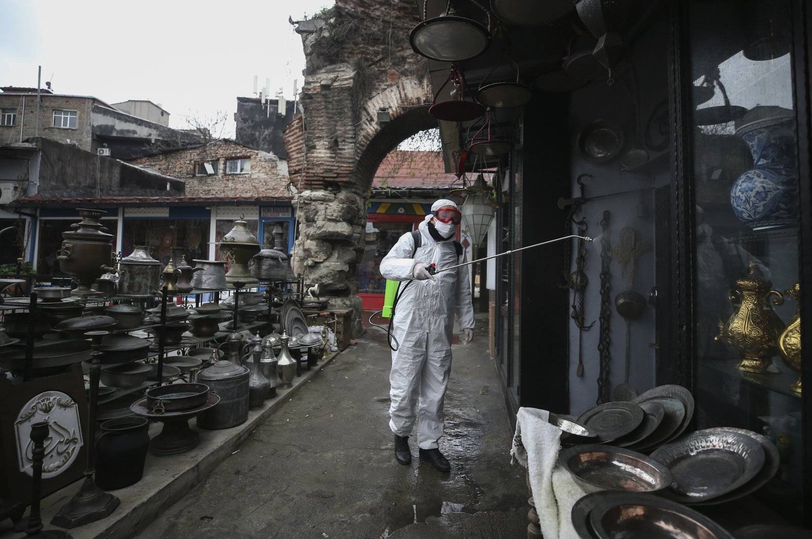 A municipality worker wearing a protective suit sprays disinfectant at the iconic Grand Bazaar in Istanbul, one of the city's main tourist attractions, that shut down amid the coronavirus outbreak, Wednesday, March 25, 2020. (AP Photo)