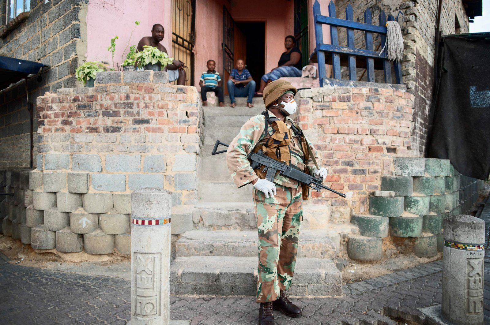 A South African National Defence Force (SANDF) soldier stands in front of a house as he patrols the streets in Alexandra, Johannesburg, on Friday, March 27, 2020 during a joint operation with the South African Police Service (SAPS) in order prevent the spread of the COVID-19 coronavirus outbreak. (AFP Photo)