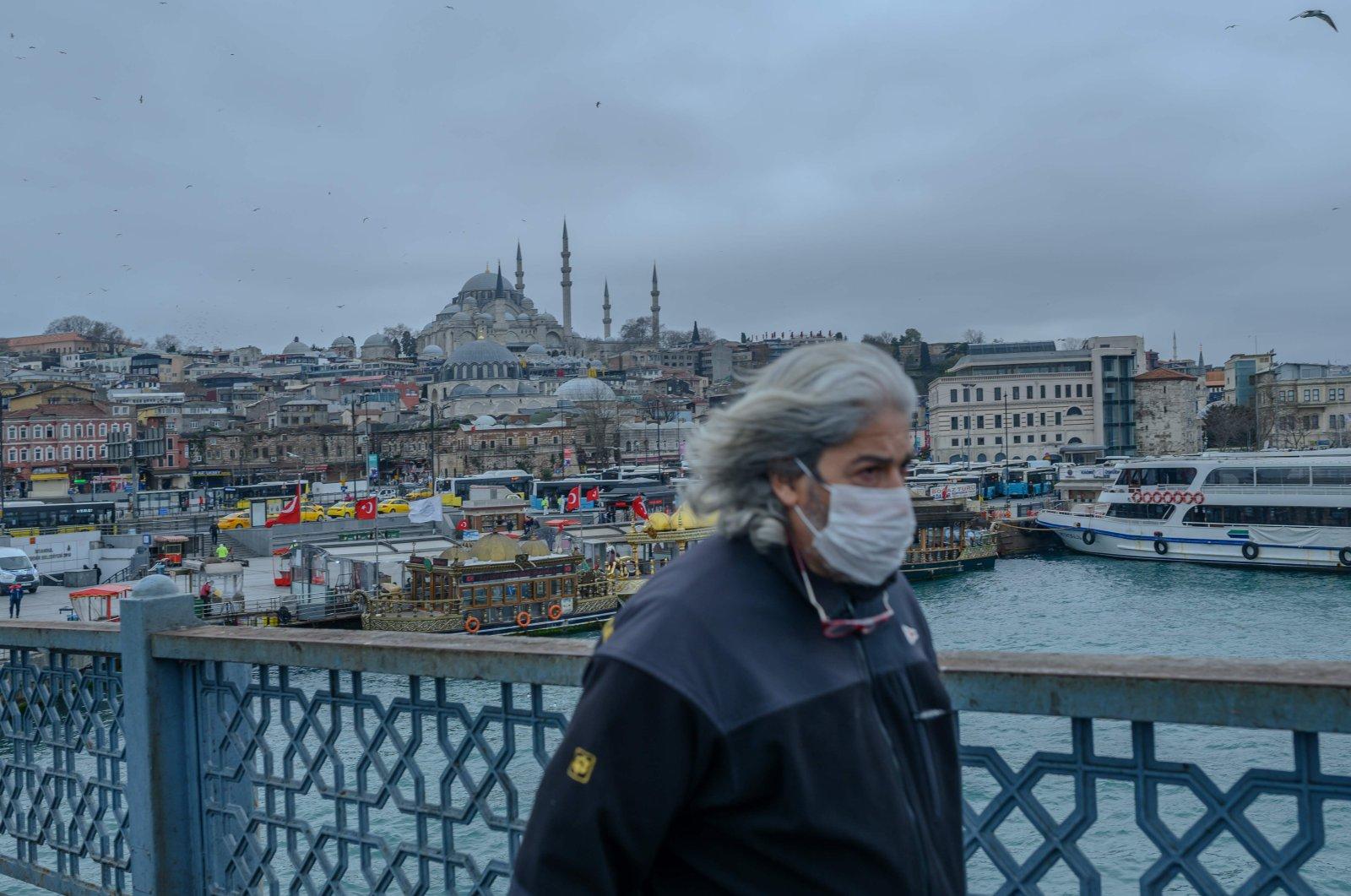 A man walks across Galata bridge in deserted central Istanbul amid coronavirus outbreak, Thursday, March 26, 2020. (AFP Photo)