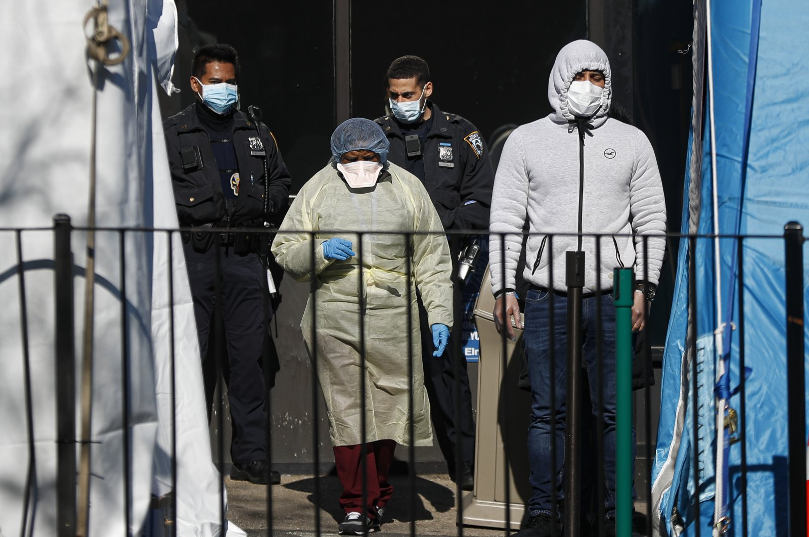 A patient, right, waits to be directed into a COVID-19 testing test by a medical worker outside Elmhurst Hospital Center, Friday, March 27, 2020, in New York. (AP Photo)