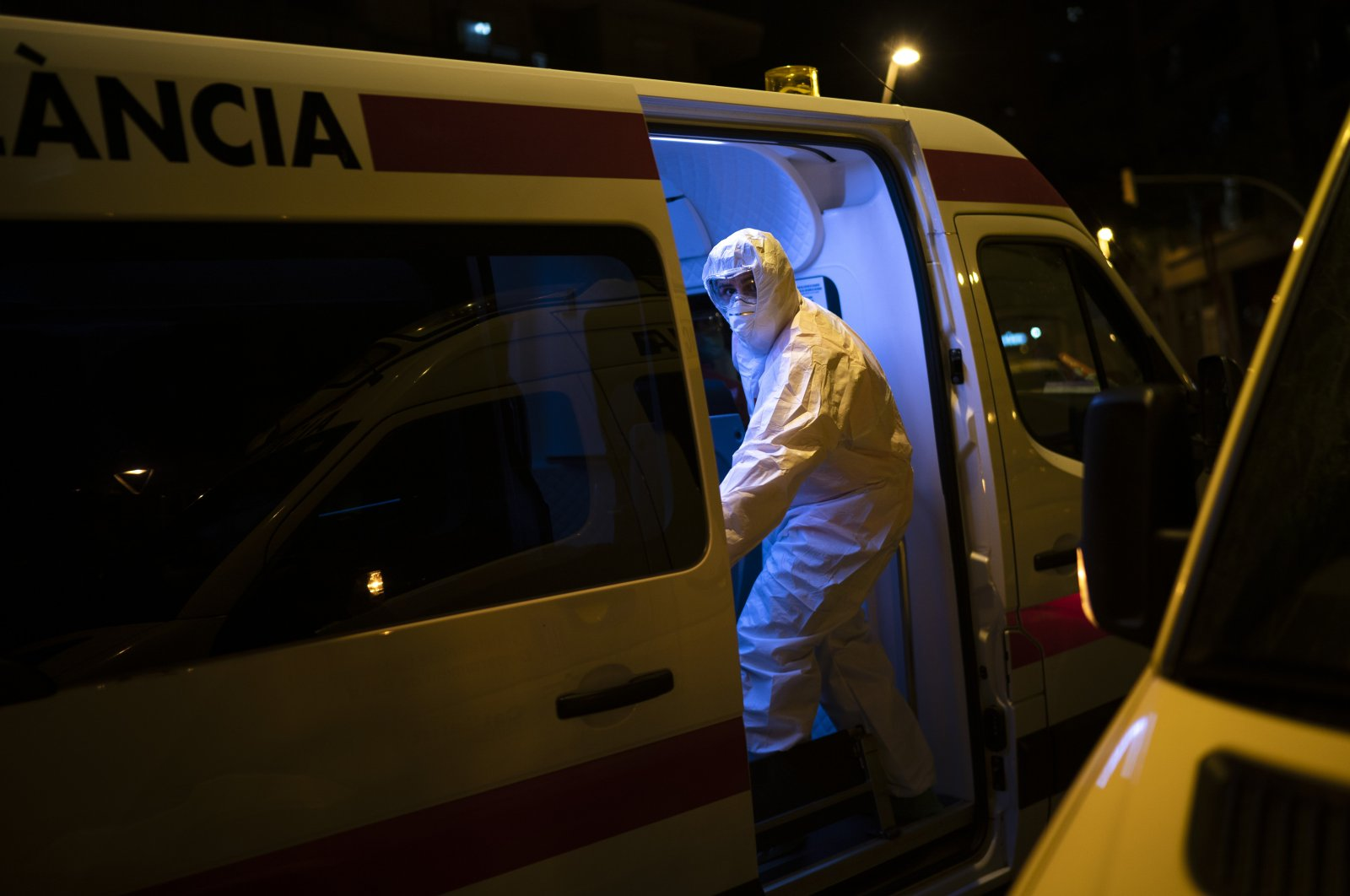 An emergency worker wearing a protective suit closes the door of an ambulance transferring a COVID-19 patient in Barcelona, Spain, Friday, March 27, 2020. (AP Photo)