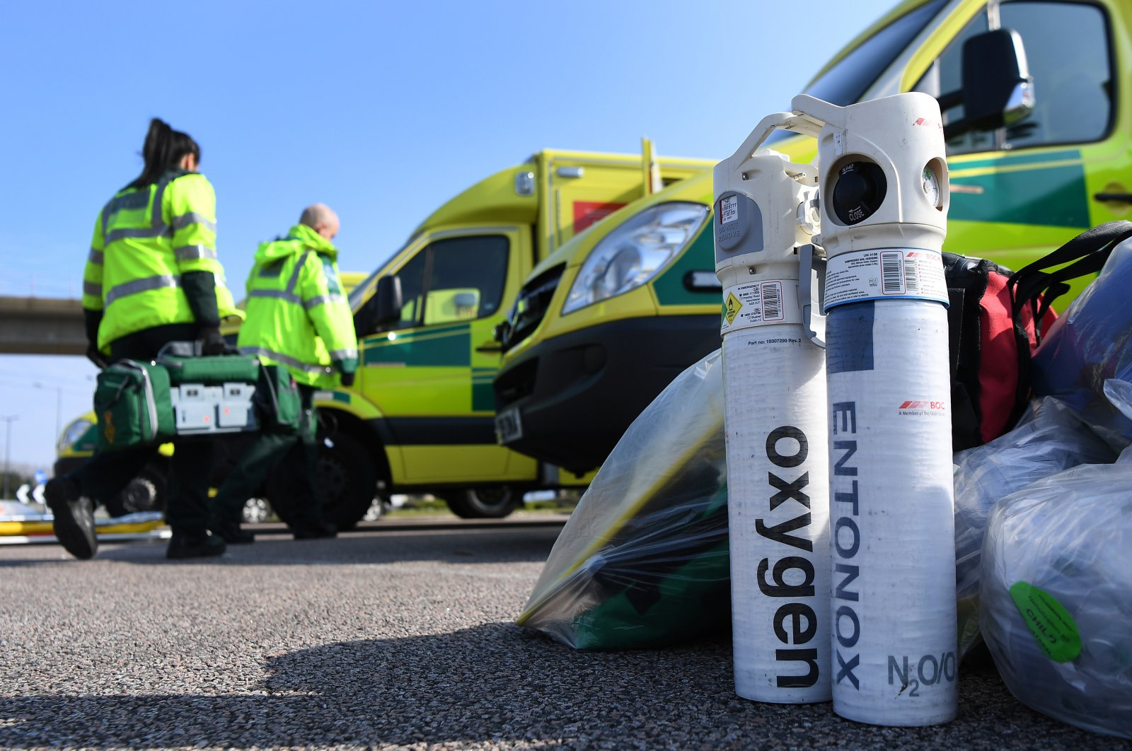 Ambulance workers unload oxygen tanks outside the ExCel Center in London, Saturday, March 28, 2020. (EPA Photo)