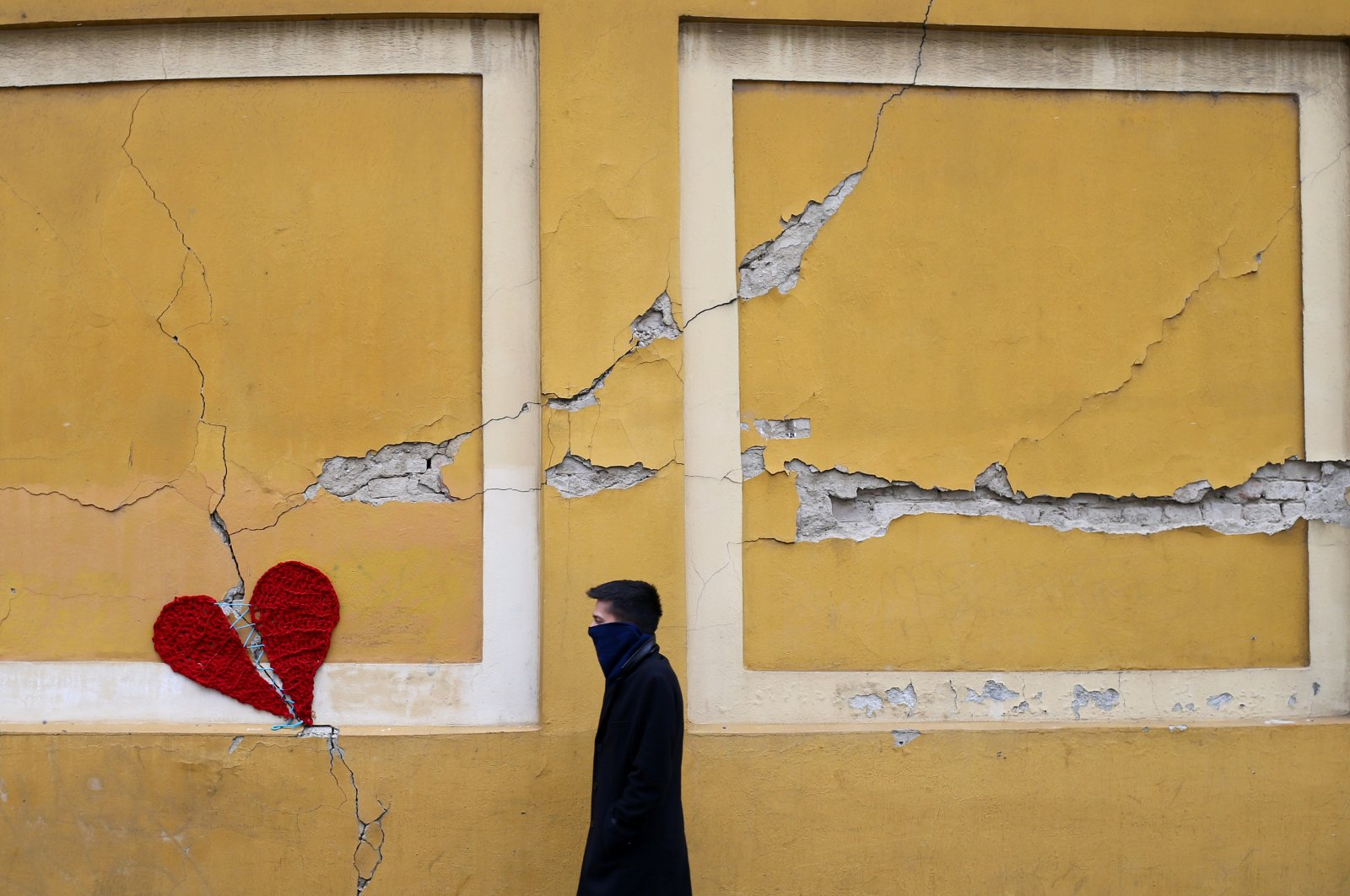 A man walks next to a repaired broken heart made of wool by Croatian designer Ivona, put on a building in downtown Zagreb, Croatia, March 25, 2020, as the country is fighting coronavirus disease (COVID-19) outbreak and the aftermatch of an earthquake that hit the country on March 22. (Reuters Photo)