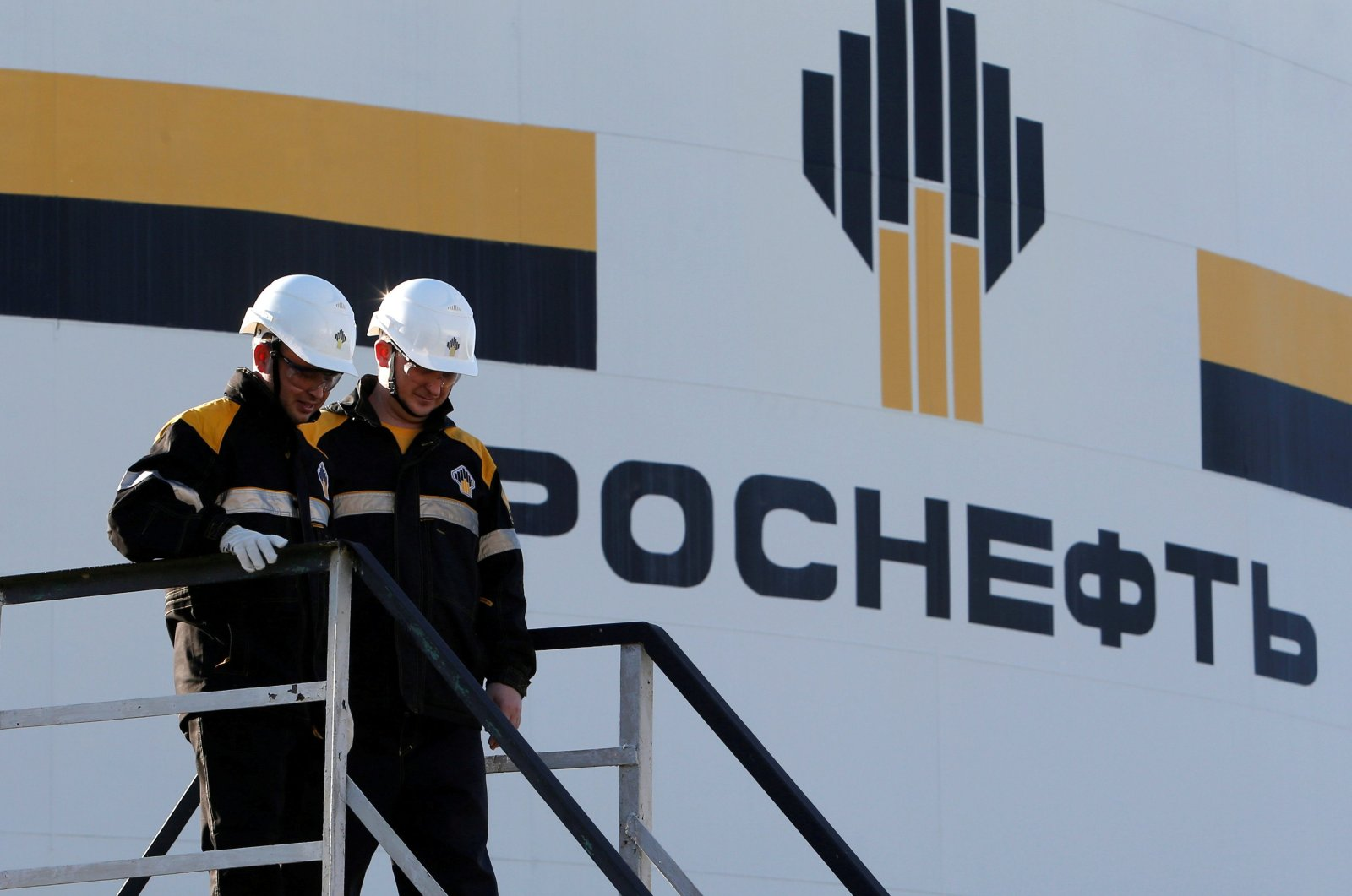 Workers stand next to logo of Russia's Rosneft oil company at central processing facility of Rosneftowned Priobskoye oil field outside Nefteyugansk, Russia, August 4, 2016. (REUTERS Photo)