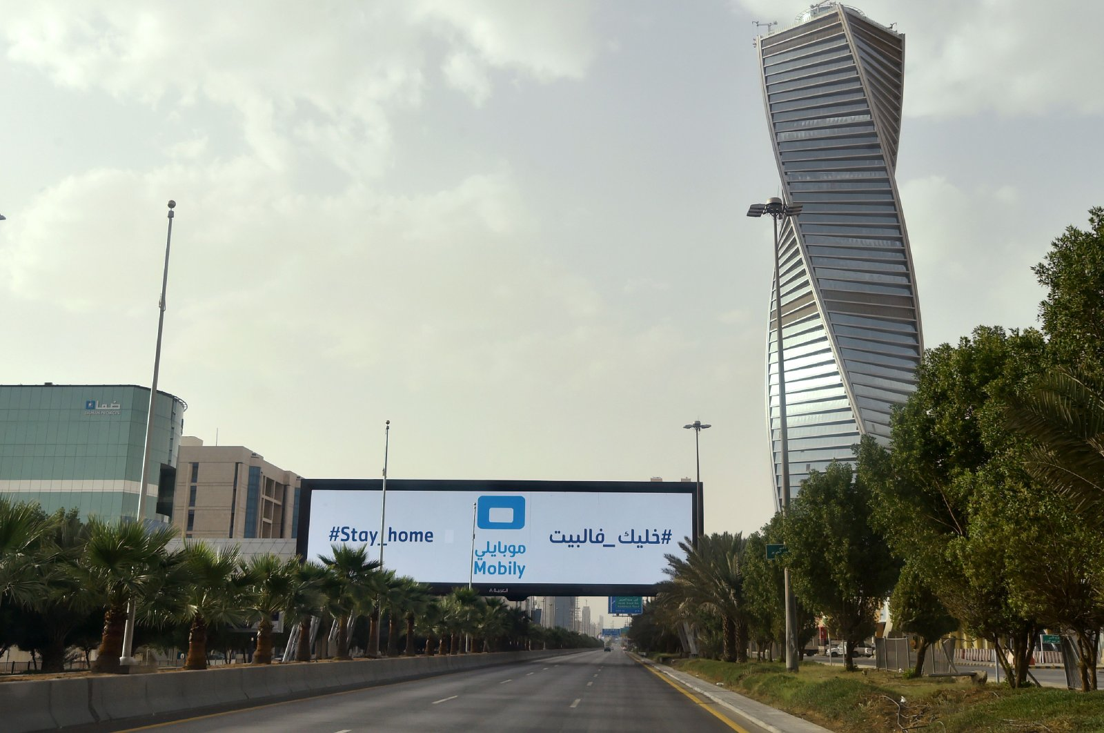 A picture taken on March 26, 2020, shows a billboard in an empty King Fahad main street in the Saudi capital Riyadh. (AFP Photo)