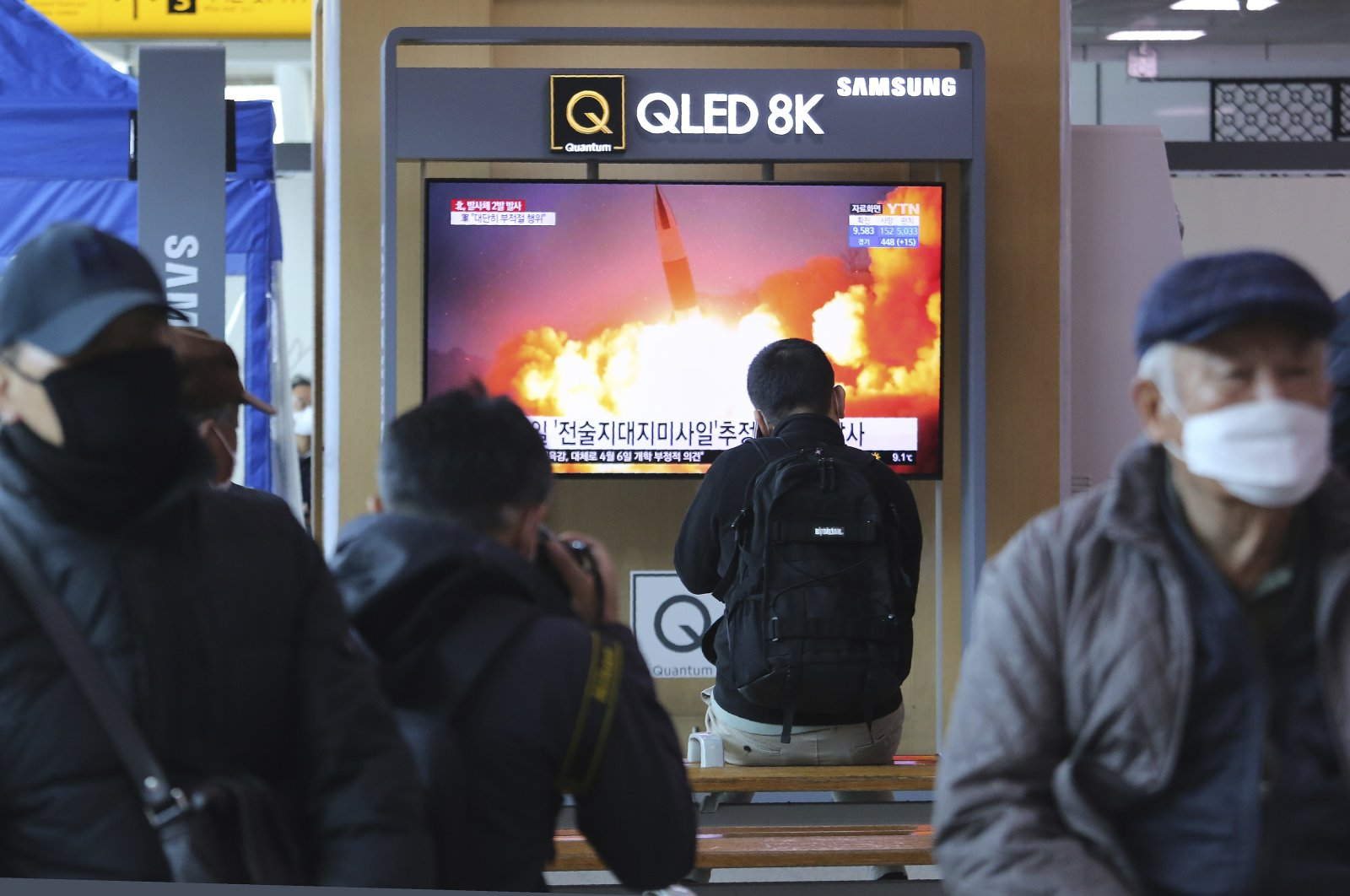 People watch a TV screen showing a file image of North Korea's missile launch during a news program at the Seoul Railway Station in Seoul, South Korea, Sunday, March 29, 2020. (AP Photo)