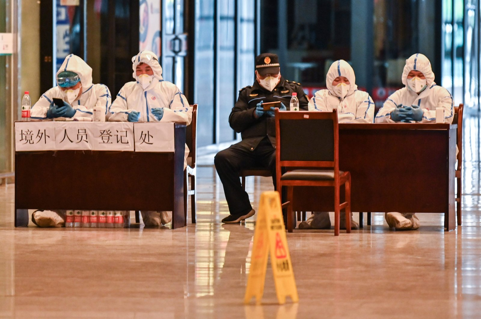 Workers in protective gear wait for passengers arriving at the railway station, Wuhan, March 28, 2020. (AFP Photo)