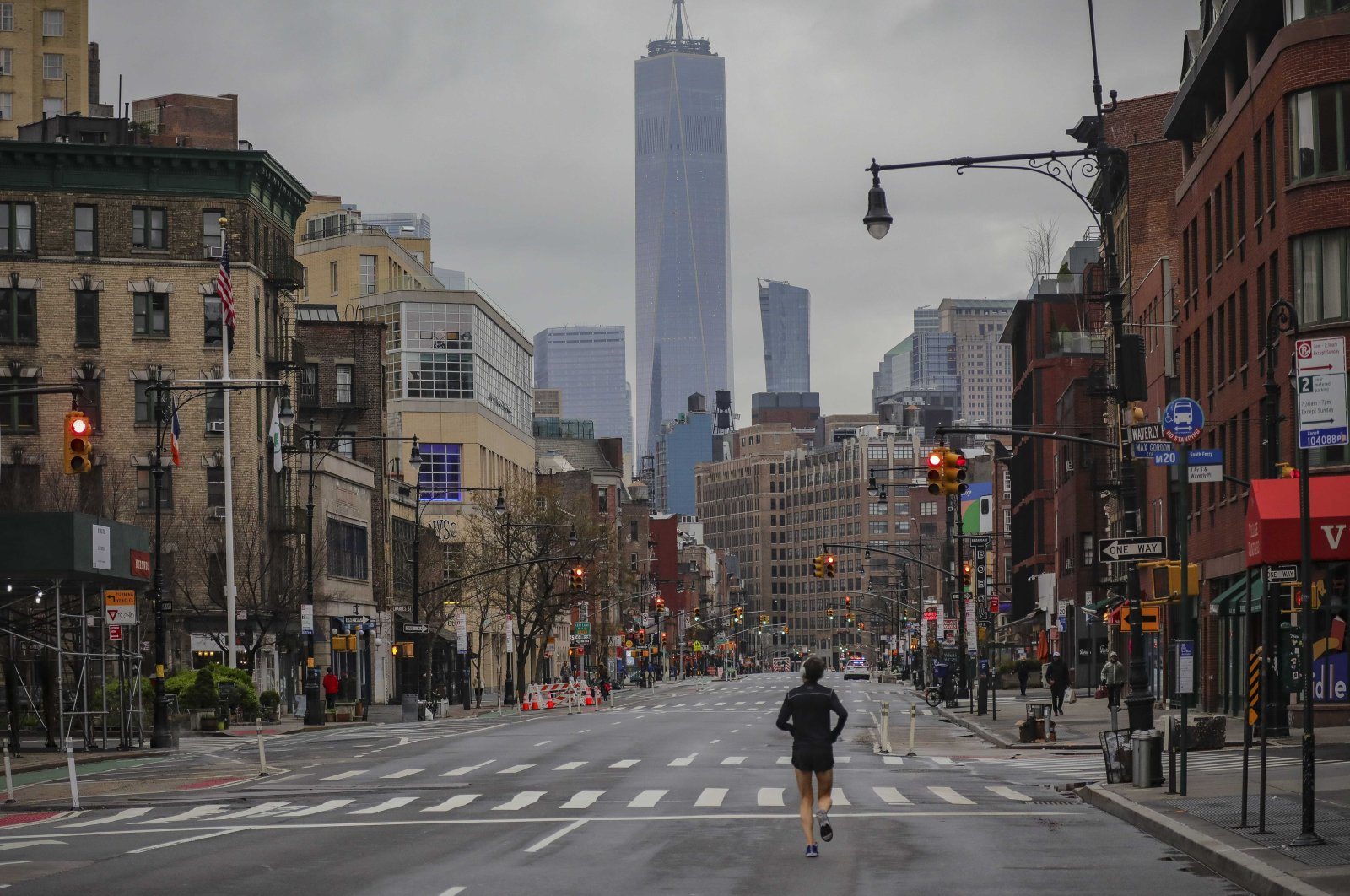 A lone jogger run on a partially empty 7th Avenue, resulting from citywide restrictions calling for people to stay indoors and maintain social distancing in an effort to curb the spread of COVID-19, in New York, Saturday, March 28, 2020. (AP Photo)