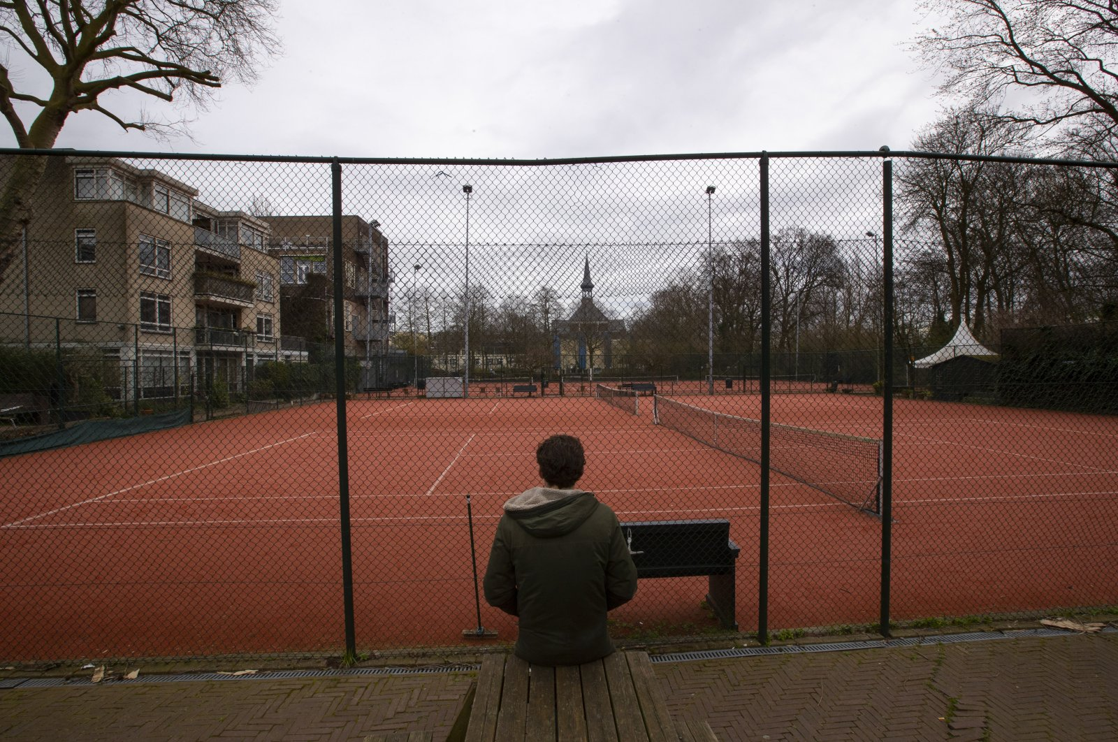 A man talks on his mobile phone outside a closed tennis club in Amsterdam, Netherlands, Wednesday, March 18, 2020. (AP Photo)