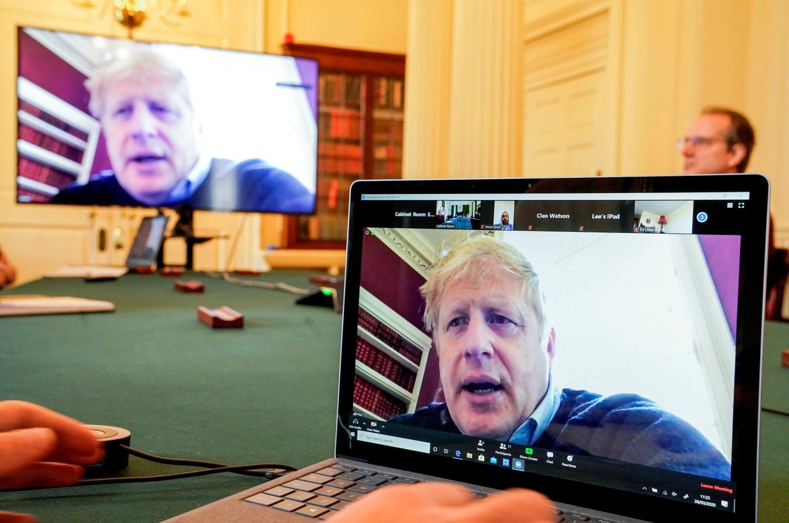 Britain's Prime Minister Boris Johnson appears on monitors for a coronavirus disease meeting, London, Saturday, March 28, 2020. (REUTERS Photo)