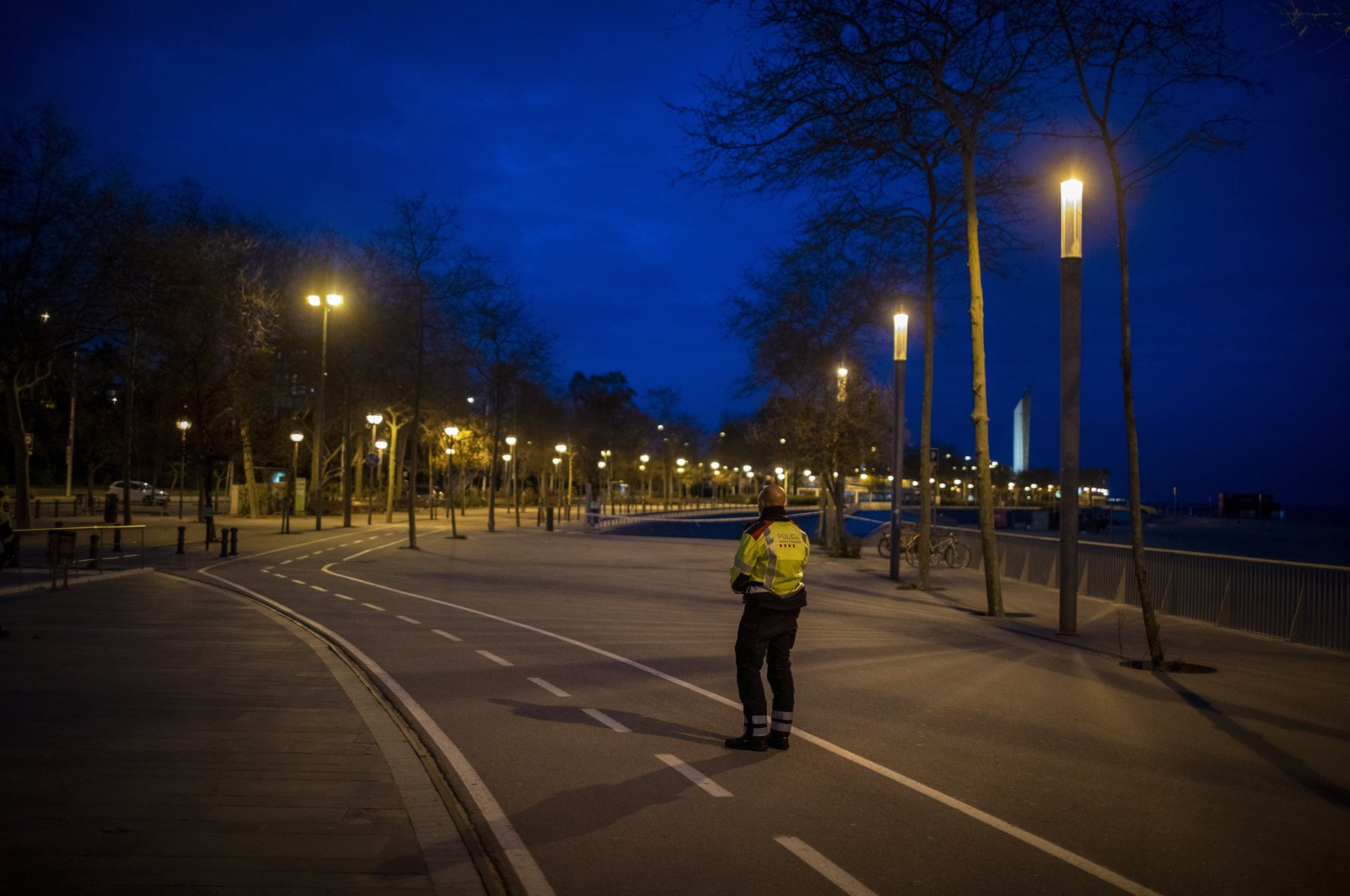 A Catalan police officer stands guard in an empty promenade in Barcelona, Spain, Saturday, March 28, 2020. (AP Photo)