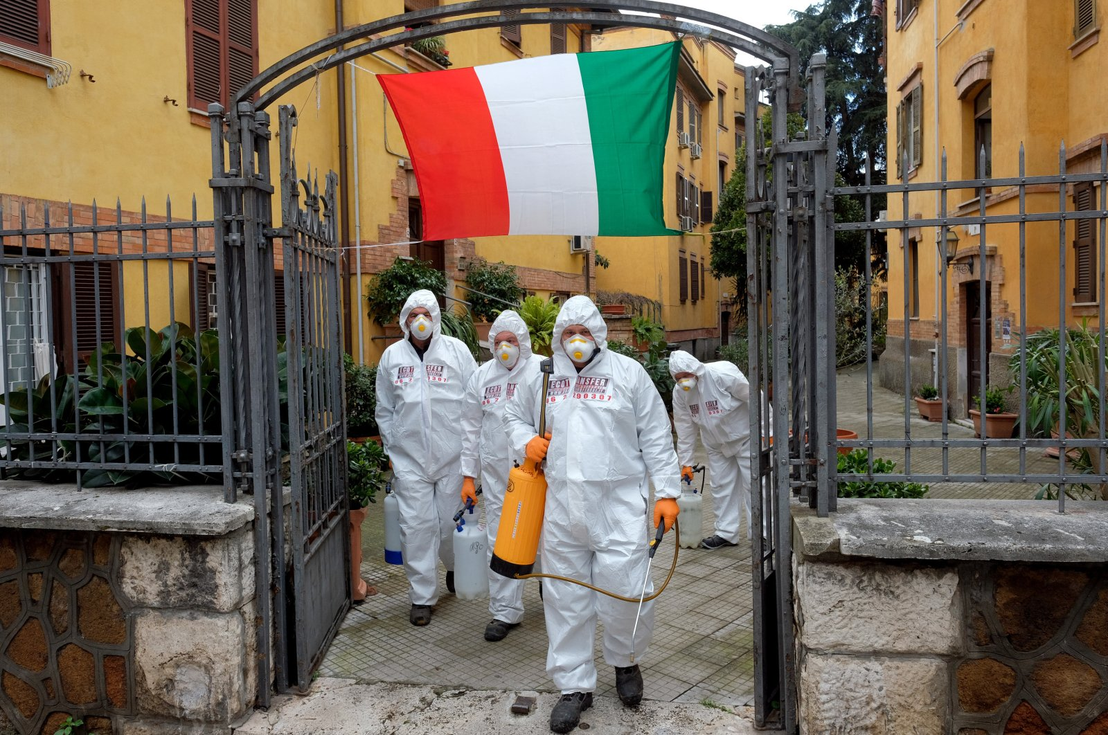 Workers wearing protective outfits sanitize a neighborhood to contain the spread of the coronavirus, Rome, Saturday, March 28, 2020. (AP Photo)