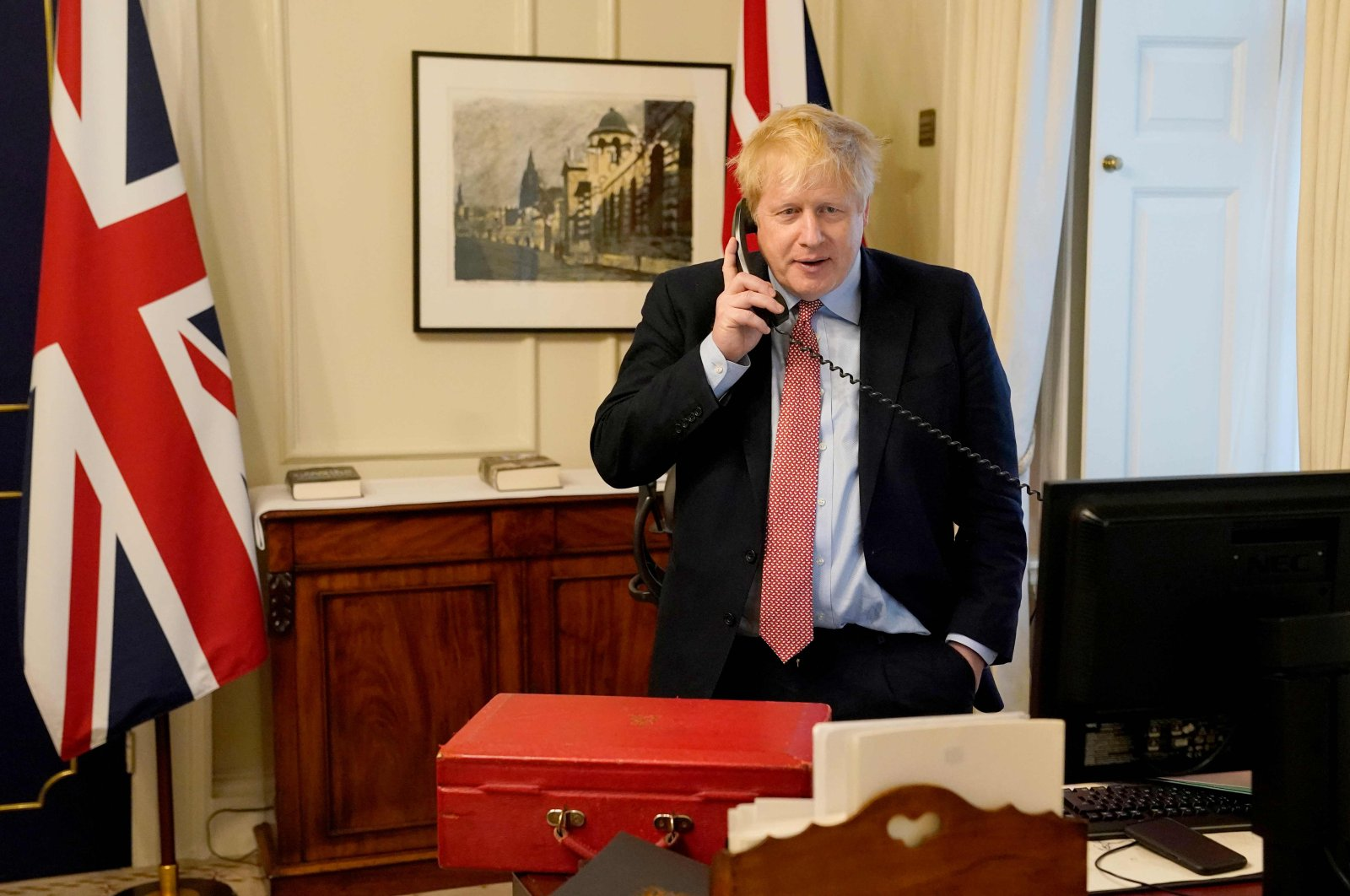 Britain's Prime Minister Boris Johnson on the telephone in his office in 10 Downing Street, to Queen Elizabeth II for their weekly audience during the coronavirus crisis, Wednesday, March 25, 2020. (AFP Photo)
