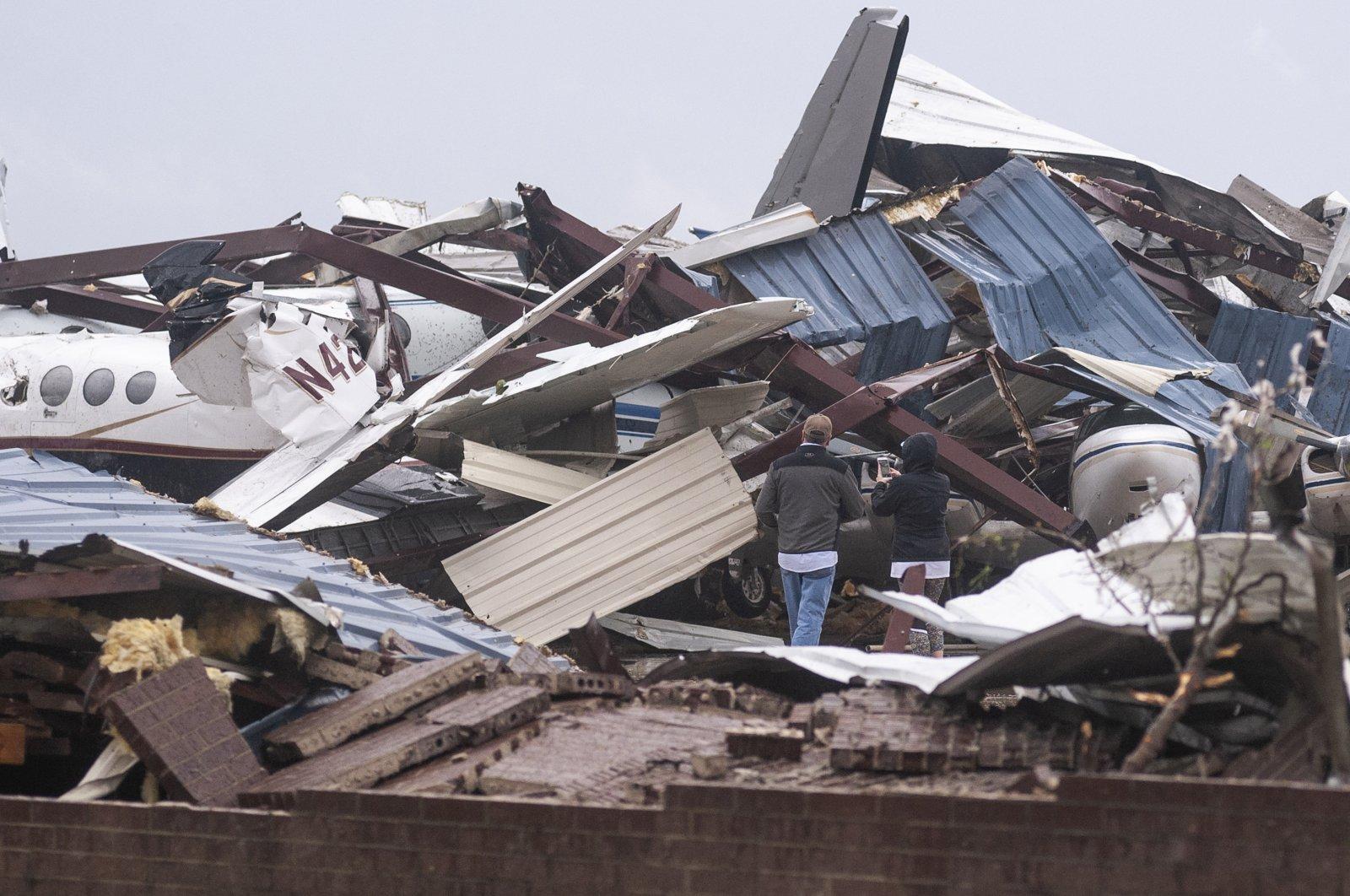 People survey damage to buildings and airplanes after a tornado at Jonesboro Municipal Airport in Jonesboro, Arkansas, the U.S., Saturday, March 28, 2020. (AP Photo)