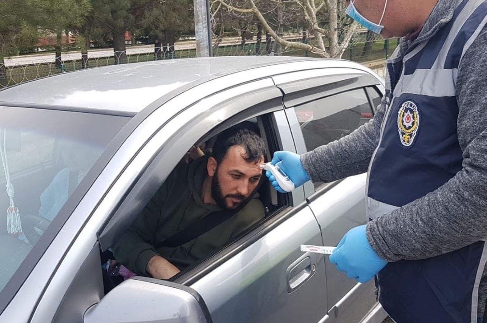 A police officer checks the temperature of a driver in Kırklareli, Turkey, Saturday, March 28, 2020. (İHA Photo)