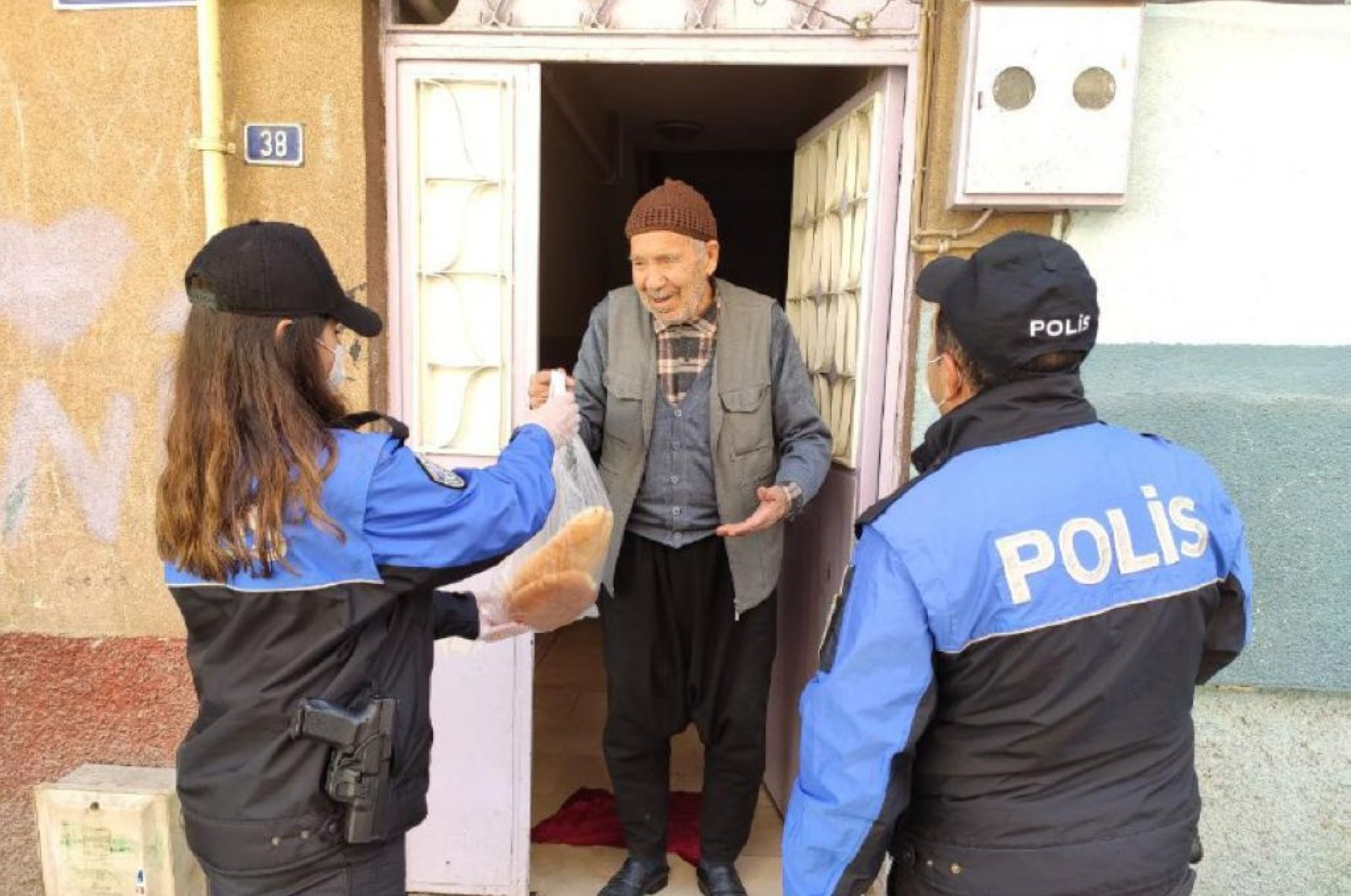 Police officers deliver bread to an elderly man in Gaziantep, Turkey, Wednesday, March 25, 2020. (AA Photo)