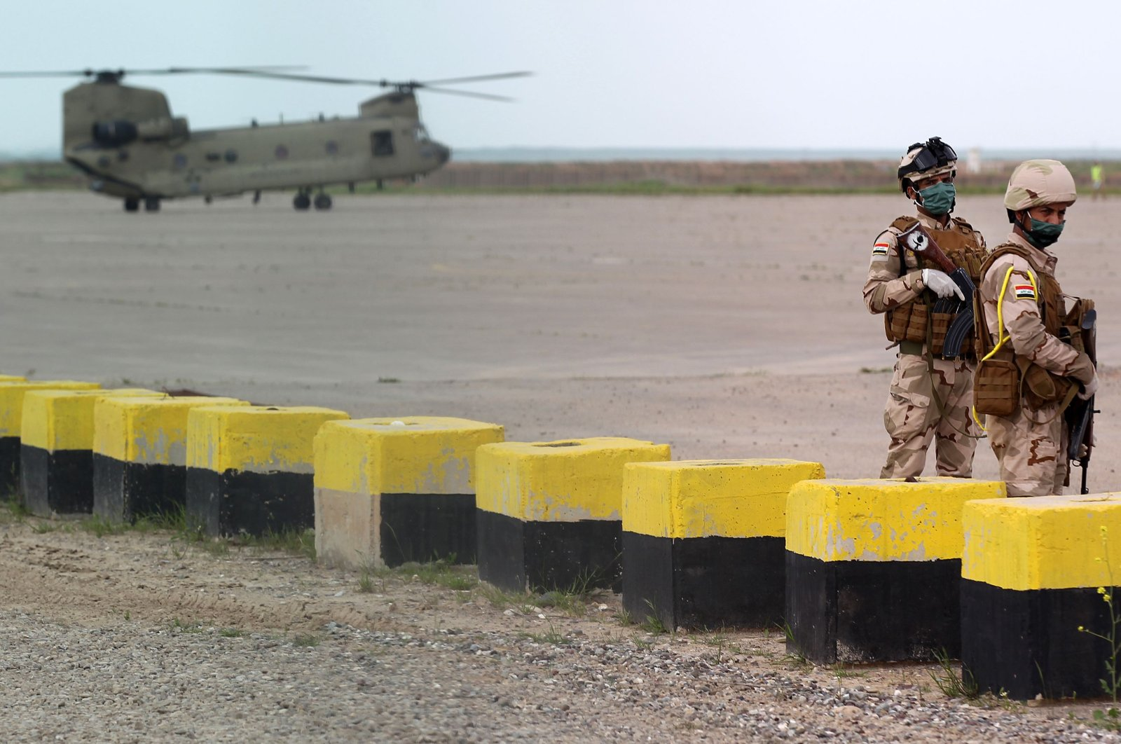 Iraqi soldiers stand guard in front of a U.S. military helicopter at the Qayyarah air base, Thursday, March 26, 2020. (AFP Photo)