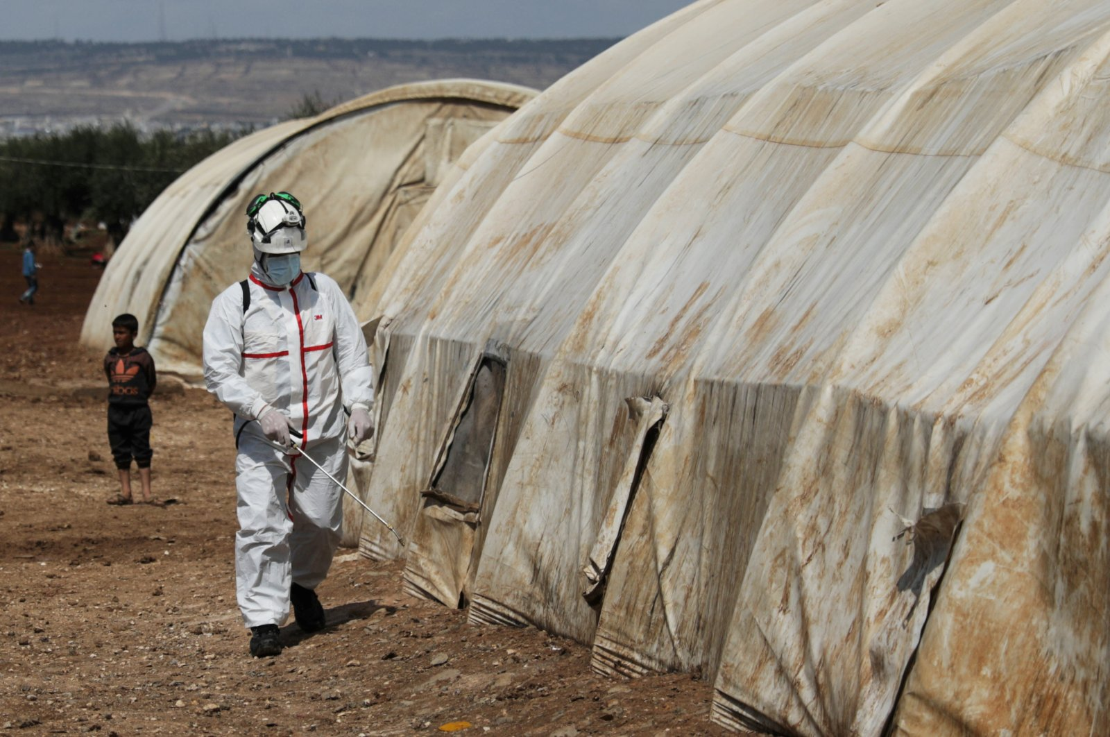 A member of the Syrian Civil Defense sanitizes a tent at the Bab Al-Nour internally displaced persons camp, Azaz, March 26, 2020. (REUTERS Photo)