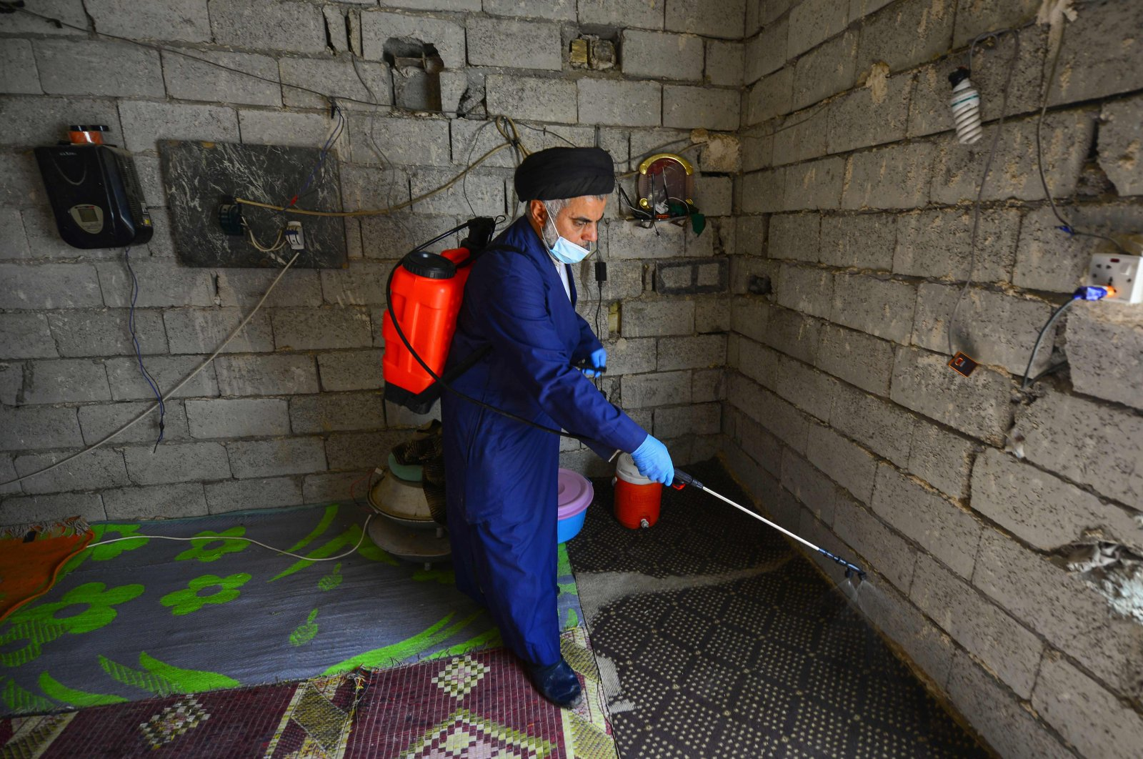 A Shiite cleric disinfects a house in an impoverished neighborhood in the central Iraqi holy city of Najaf on Monday, March 23, 2020, amid the COVID-19 coronavirus pandemic. (AFP File Photo)