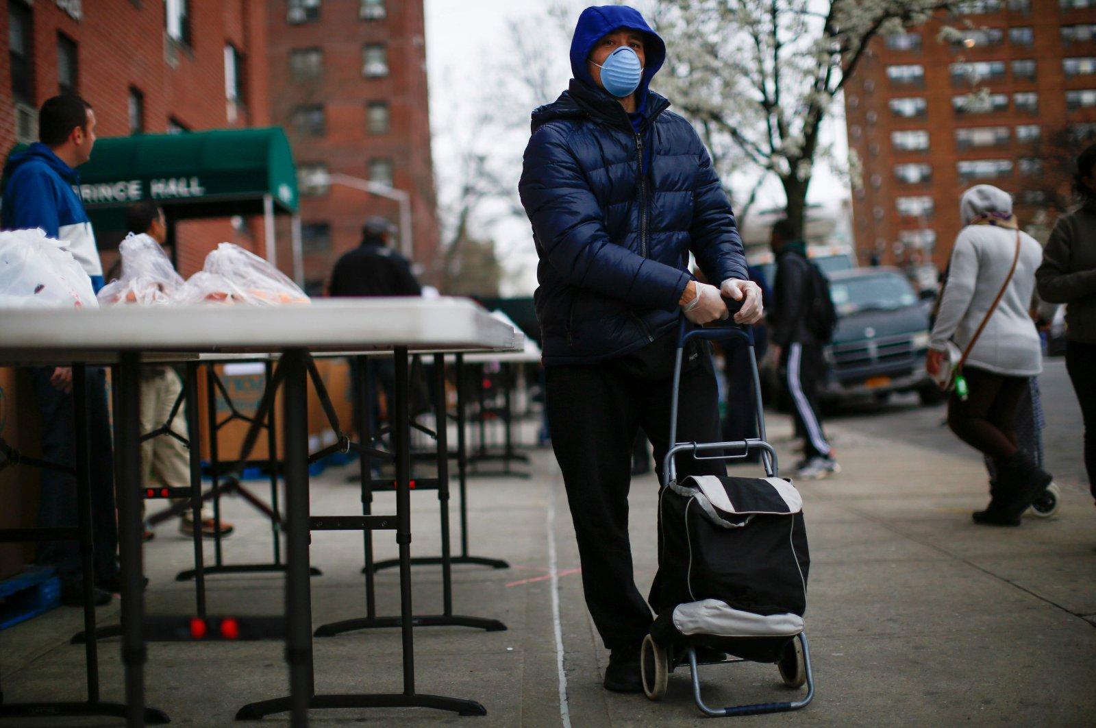A man carries bags of groceries as volunteers distribute food in Harlem, New York City, Saturday, March 28, 2020. (AFP Photo)