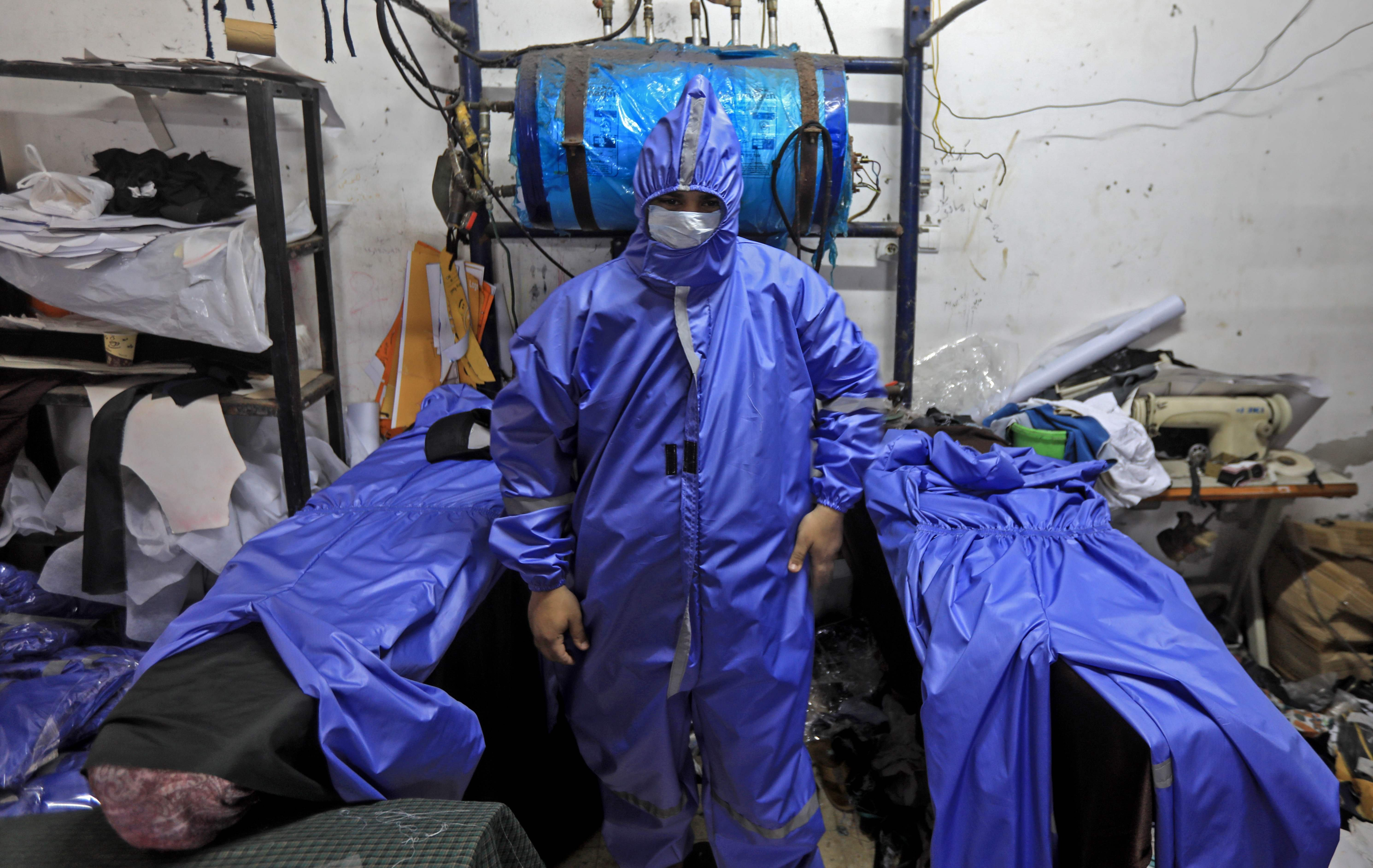 Palestinian workers manufacture protective coverall suits and masks at a workshop in Gaza City on Monday, March 30, 2020, amid the COVID-19 pandemic. (AFP Photo)