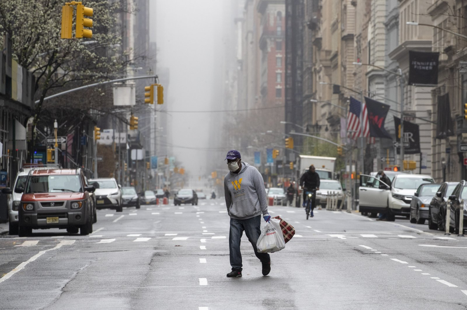 A man wearing a face mask walks across the middle of 5th Avenue in Midtown Manhattan, New York City, Sunday, March 29, 2020. (AP Photo)