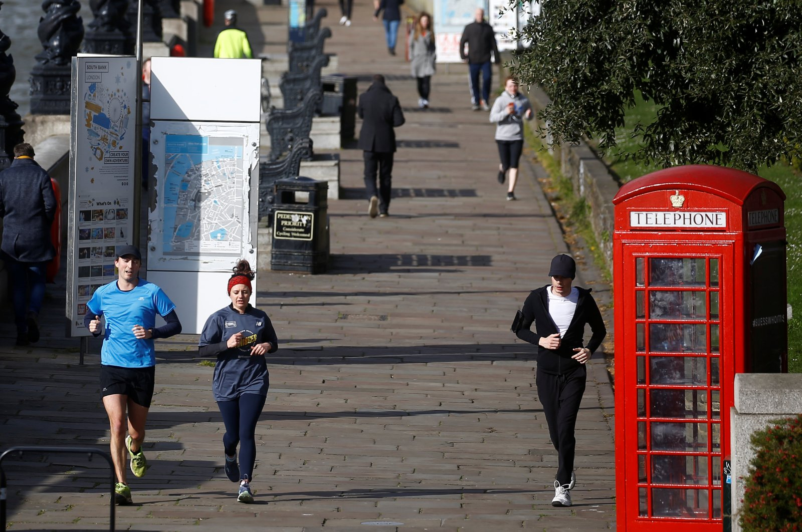 Joggers are seen on South Bank, London, March 29, 2020. (REUTERS Photo)