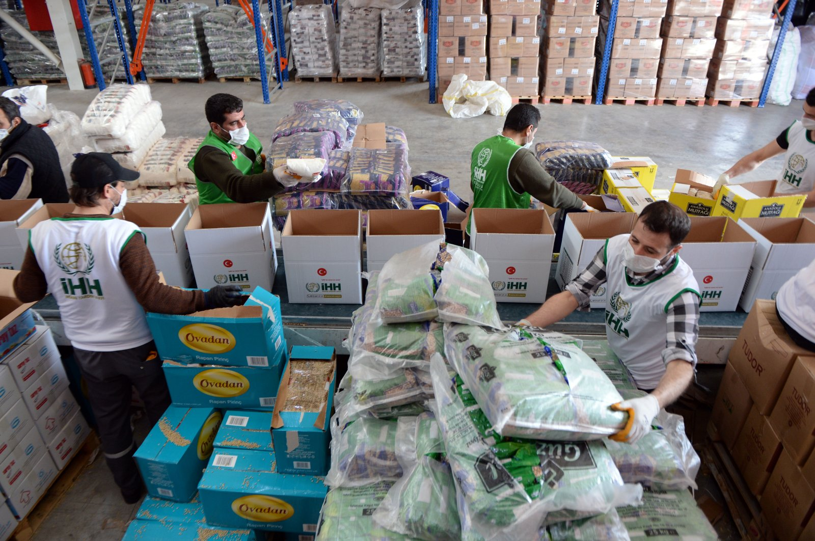 Aid workers at the IHH load packages to be distributed to the needy as part of coronavirus relief efforts, Friday, March 27, 2020. (AA Photo)