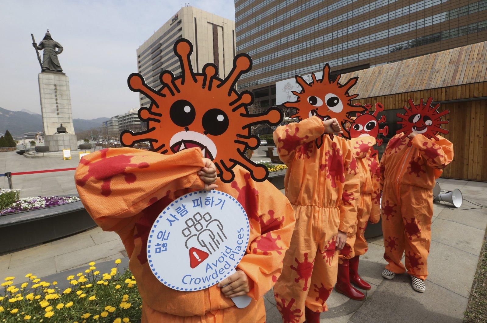 Environmental activists wear masks symbolizing a virus, Seoul, South Korea, Thursday, March 26, 2020. (AP Photo)