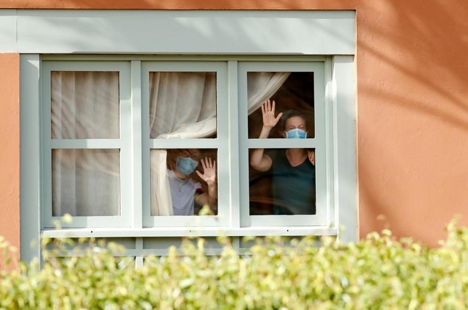 Guests, wearing protective face masks, look through a window at H10 Costa Adeje Palace, on the Spanish island of Tenerife on Wednesday, Feb. 26, 2020. (REUTERS Photo)