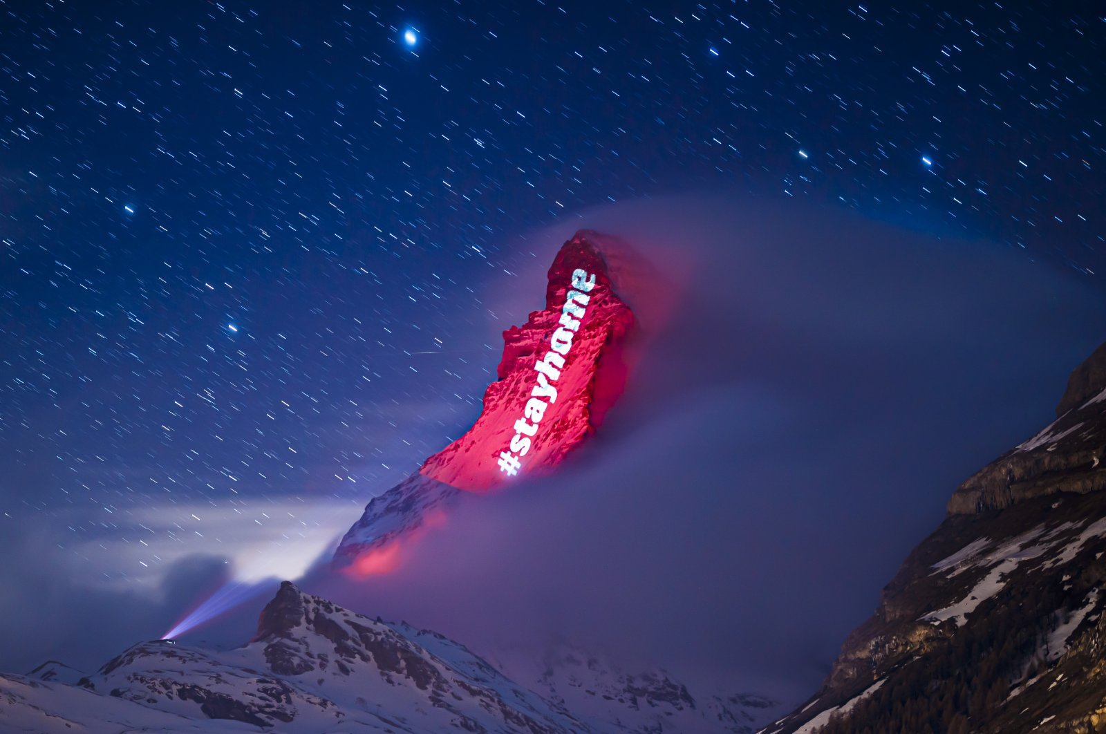 The iconic Matterhorn mountain is illuminated by Swiss light artist Gerry Hofstetter aiming to send messages of hope, support and solidarity to the ones sufferings from the global coronavirus disease, in the alpine resort of Zermatt, Switzerland, Thursday, March 26, 2020. (AP Photo)