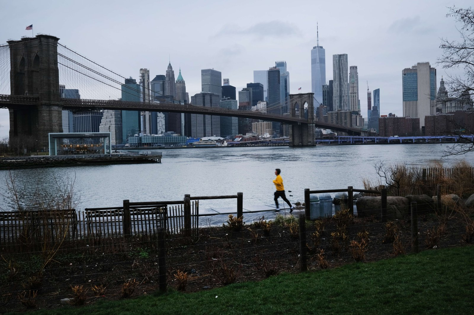 A person runs in Brooklyn while lower Manhattan looms in the background, Saturday, March 28, 2020, in New York City, New York. (AFP Photo)