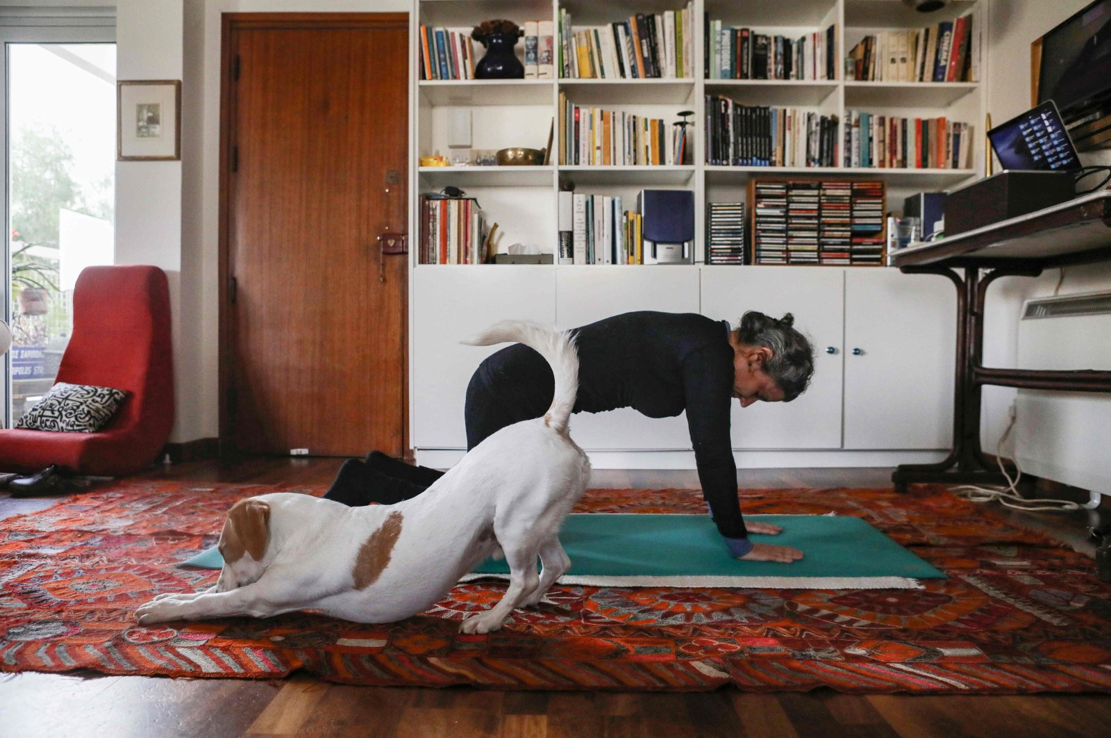 This picture taken on March 23, 2020 shows a woman taking part in an online pilates class at home, as her dog Elvis stretches next to her, in Nicosia. (AFP Photo)