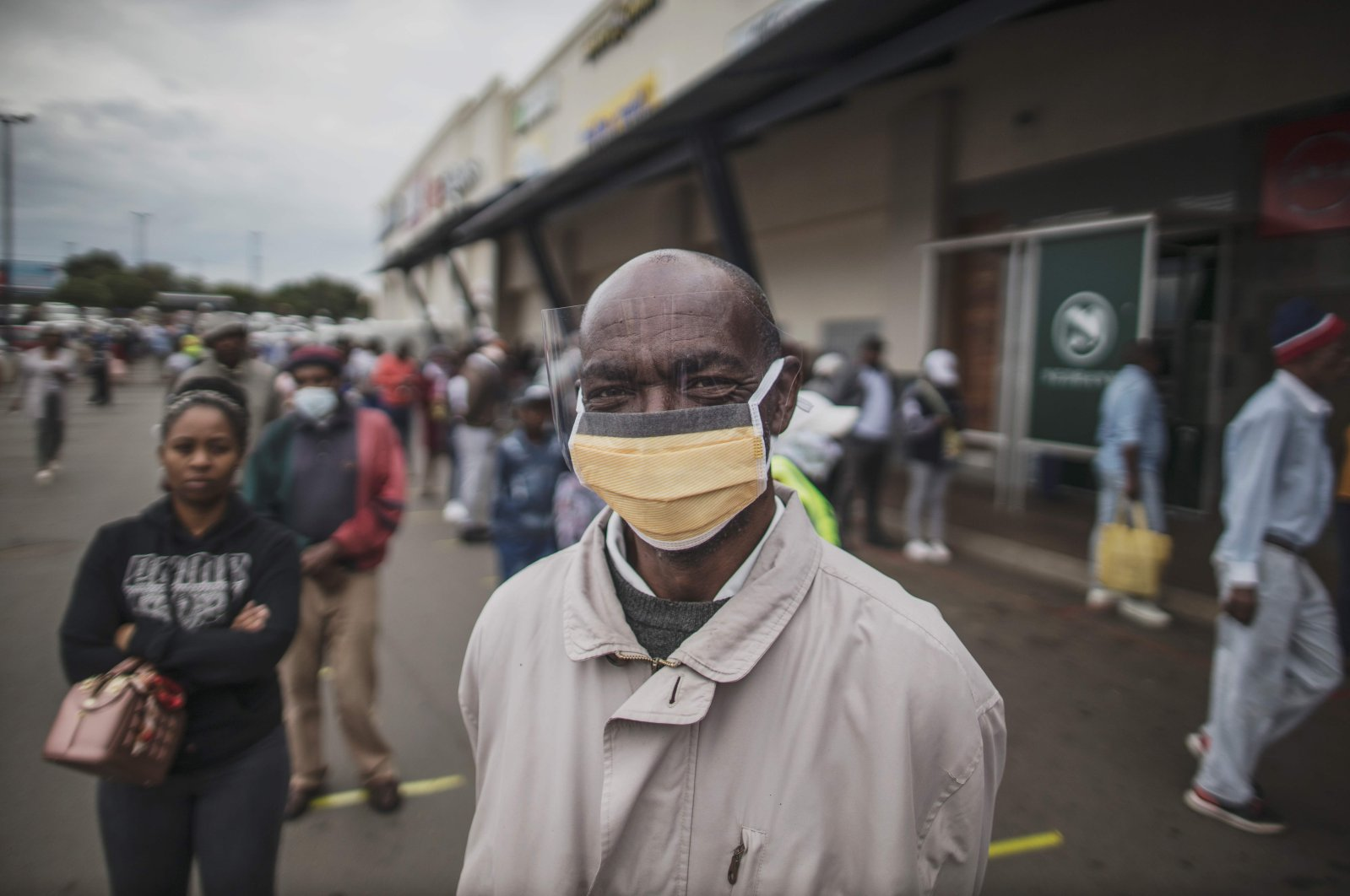 An elderly man from Soweto, covers his face with a face shield while queuing at a SASSA (South African Social Security Agency) pay-point in Soweto on March 30, 2020. (AFP Photo)