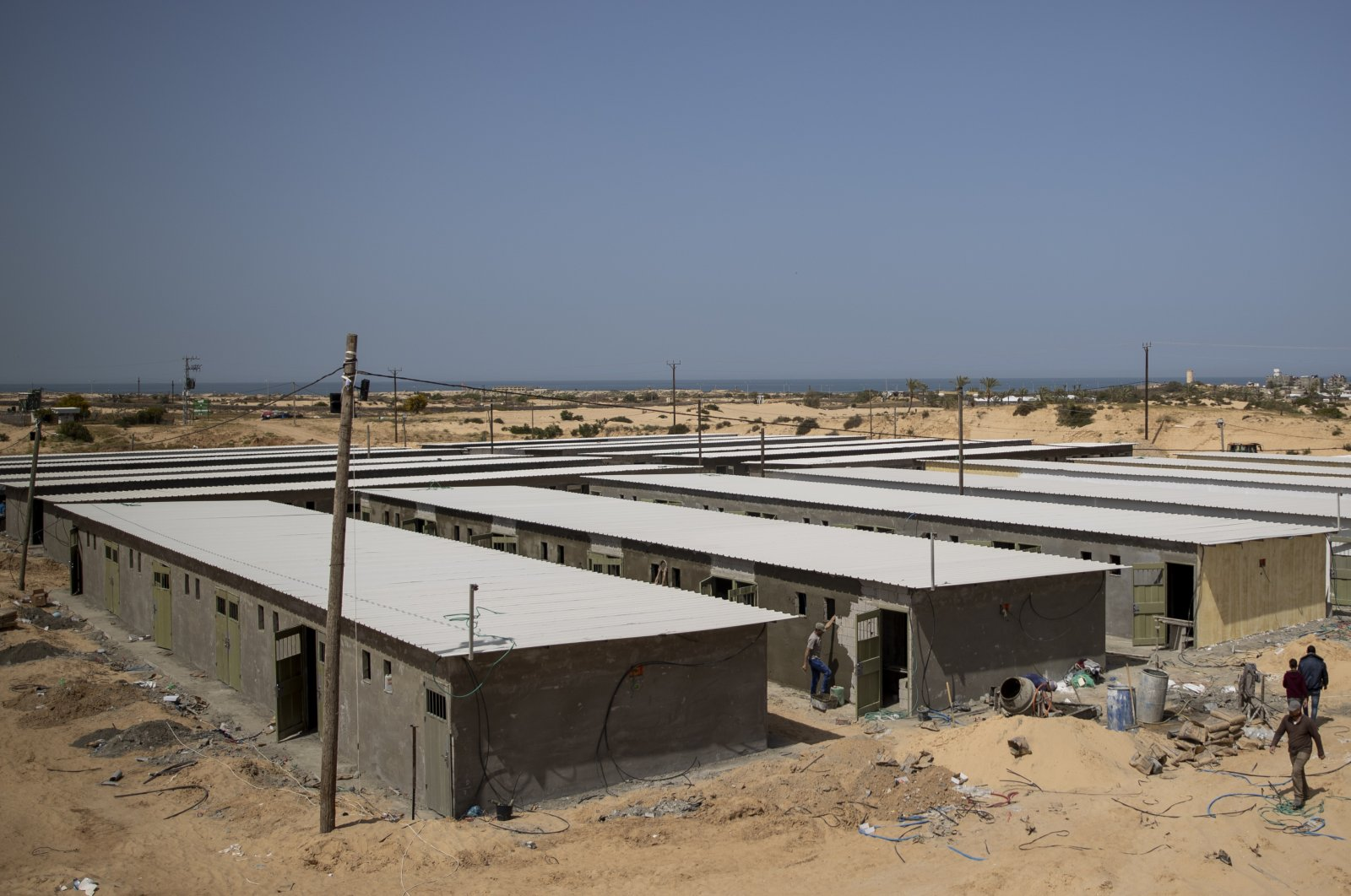 Palestinian workers construct a quarantine complex to be used for coronavirus cases, in the southern Gaza Strip, Monday, March 30, 2020. (AP Photo)