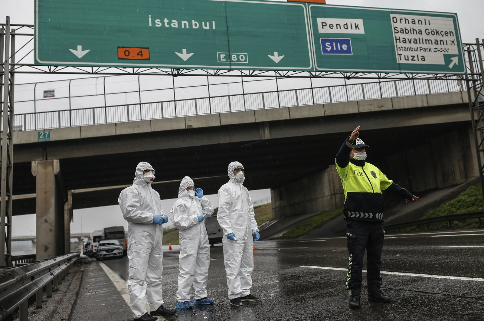 A police officer stops a bus so health officials could measure the body temperature of the passengers at a checkpoint, on the Asian side of Istanbul, Sunday, March 29, 2020. (AP Photo)