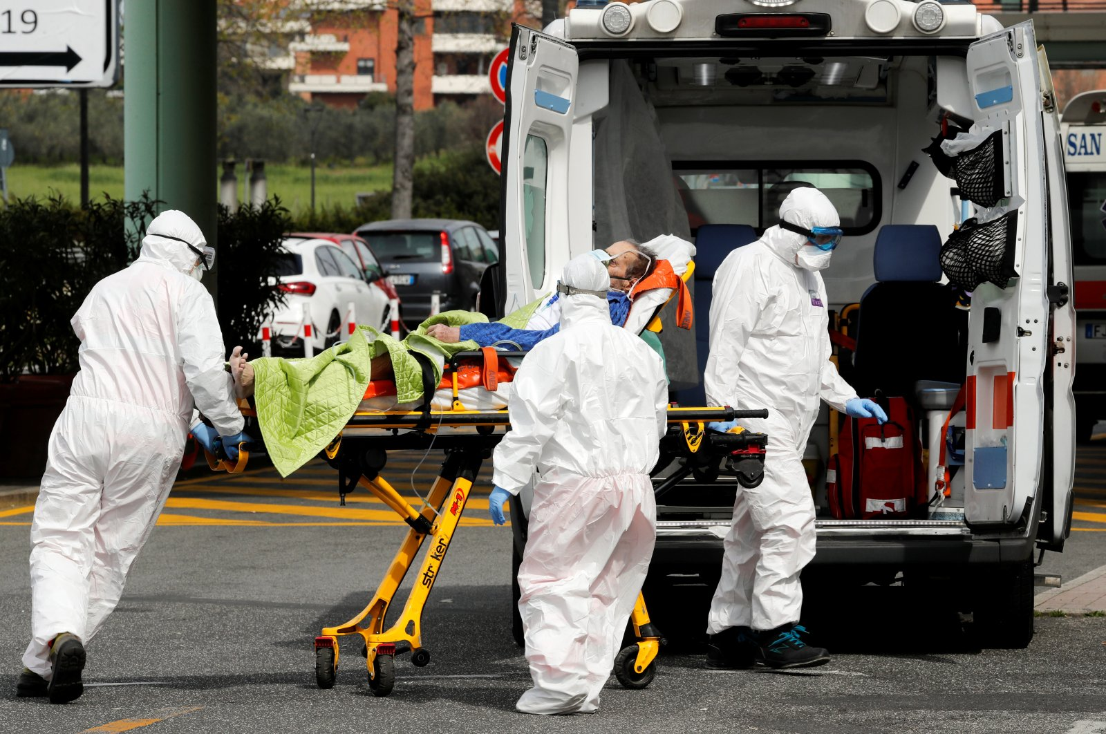 Medical workers in protective suits push a patient on a stretcher in front of the Policlinico Tor Vergata, where patients suffering from the disease caused by the novel coronavirus (COVID-19) are hosted, in Rome, Italy, Monday, March 30, 2020. (Reuters Photo)