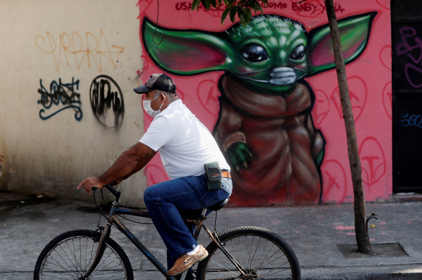 "View of graffiti drawn by artist Pulido of the character Baby Yoda, from the TV series ""The Mandalorian,"" wearing a mask and the message ""wear mask like baby Yoda"" to remind the population to take measures against the coronavirus, in Guatemala City, Guatemala, Monday, March 30, 2020. (EPA Photo)"