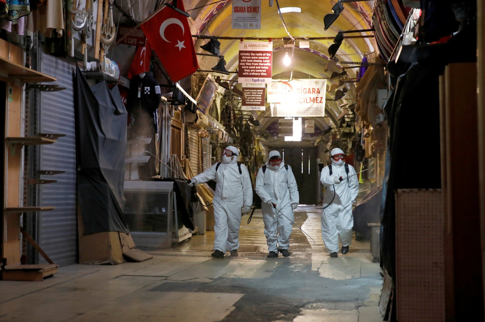 Workers in protective suits spray disinfectant at the Grand Bazaar to prevent the spread of the coronavirus disease (COVID-19), Istanbul, Turkey, Wednesday, March 25, 2020. (Reuters Photo)