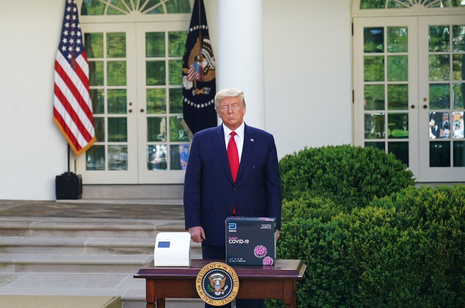 U.S. President Donald Trump stands behind a five-minute test kit for COVID-19 during the daily briefing in the Rose Garden of the White House in Washington, D.C., on Monday, March 30, 2020. (AFP Photo)