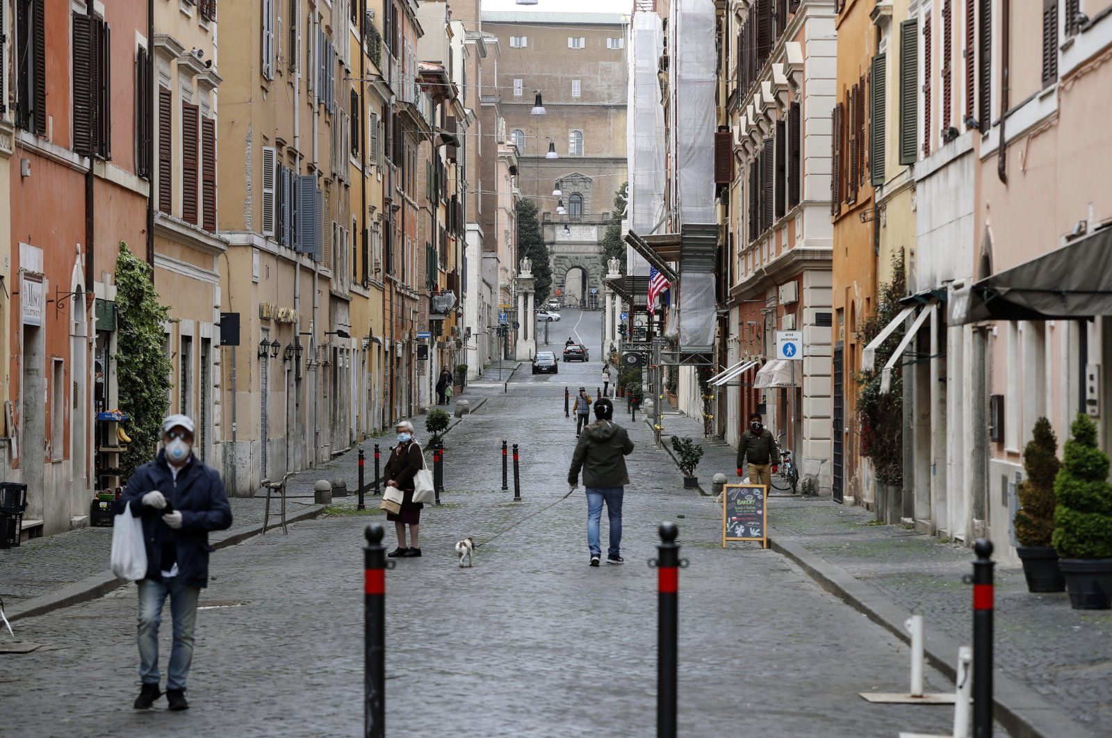 People wearing face masks walk on a street, during the coronavirus lockdown in Rome, in Borgo Pio, Italy, Monday, March 30, 2020. (EPA Photo)