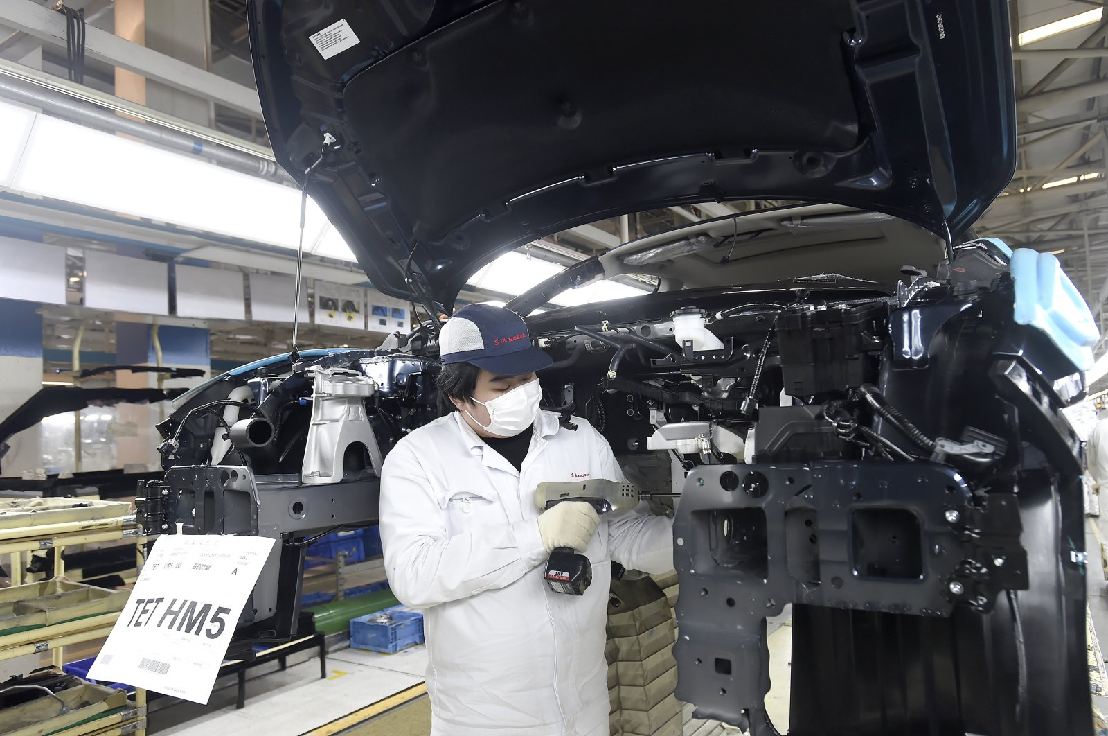 A worker wearing a face mask works on an assembly line at a Dongfeng Honda automotive manufacturing plant in Wuhan in central China's Hubei Province, Saturday, March 28, 2020. (AP Photo)